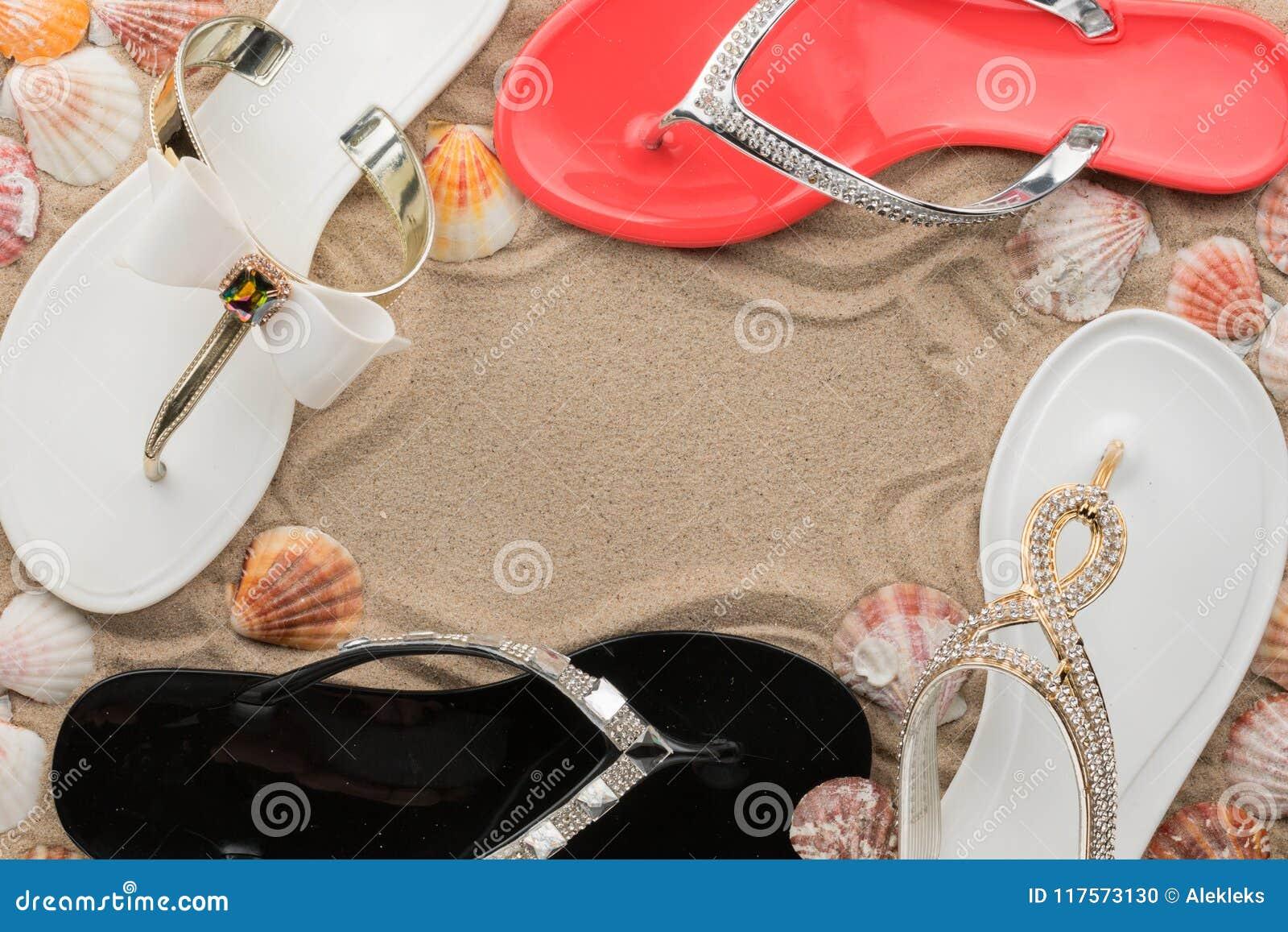 El marco lujoso hecho de chancletas, la cáscara y las estrellas de mar en la arena varan
