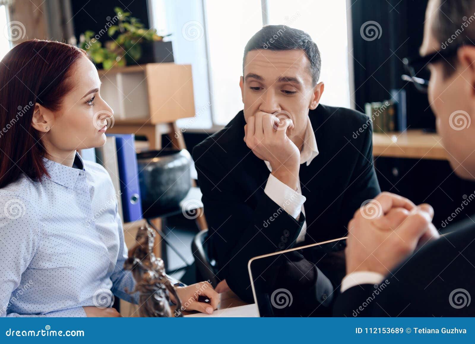 El marido descompuesto se está sentando con la esposa joven detrás de la tabla del ` s del abogado de divorcio