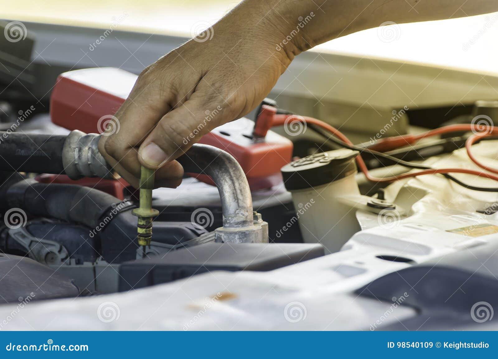 El mecánico de automóviles utiliza la mano del motor de comprobación o de fijación del técnico
