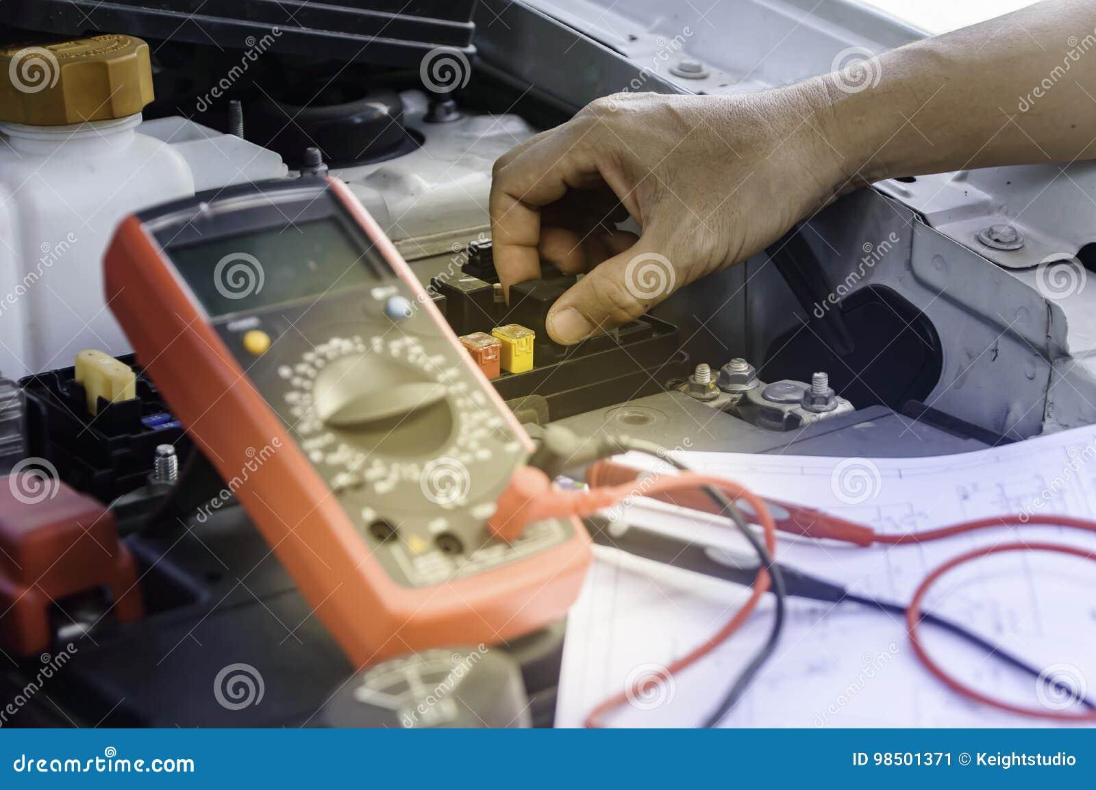 El mecánico de automóviles utiliza un voltímetro del multímetro