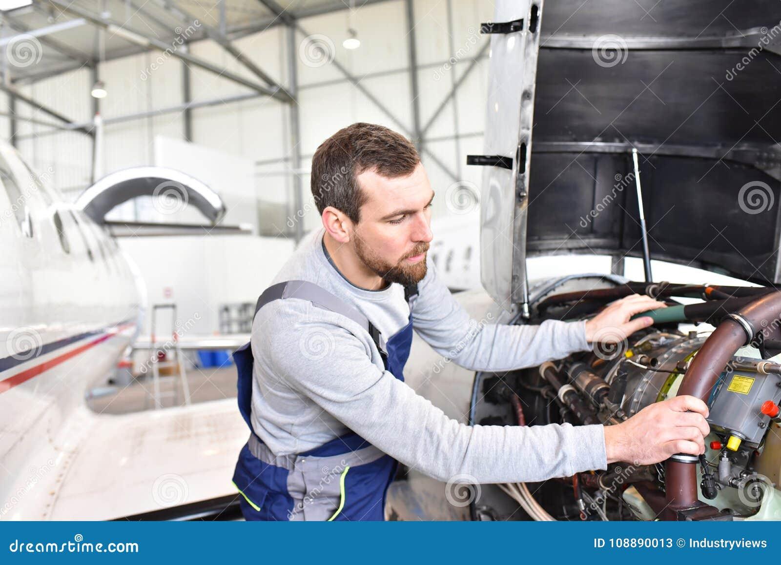 El mecánico de aviones repara un motor de avión en un hanga del aeropuerto