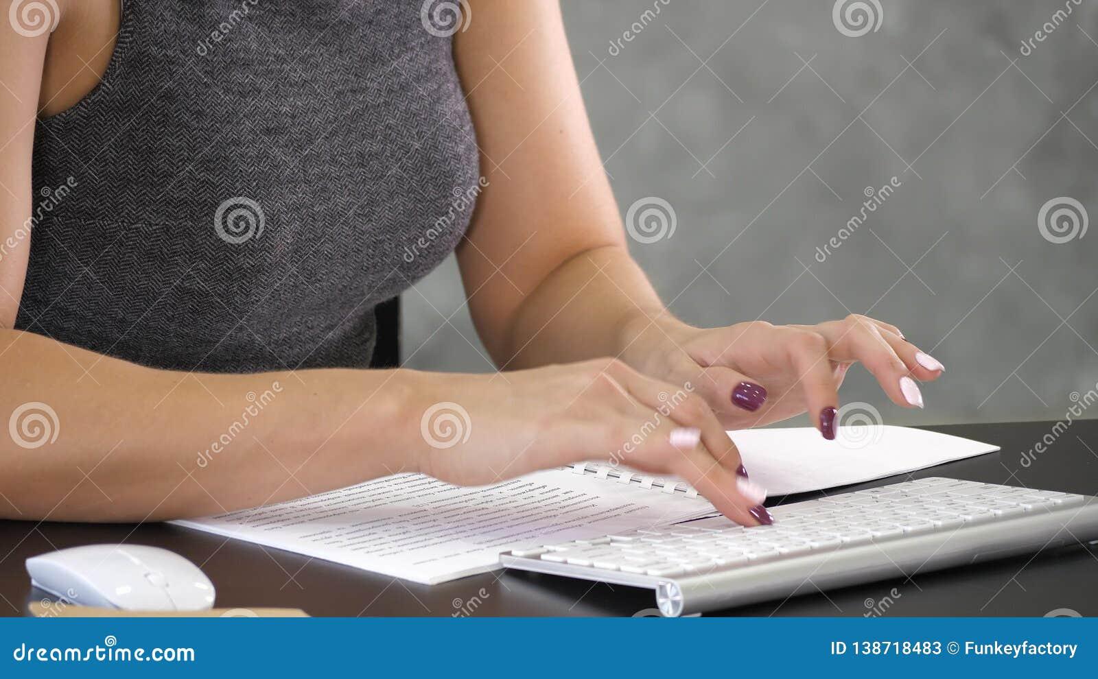 El mecanografiar ocupado de las manos femeninas en un teclado