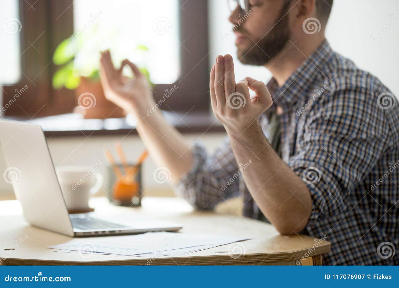 El meditar masculino concentrado en la oficina que alivia la tensión