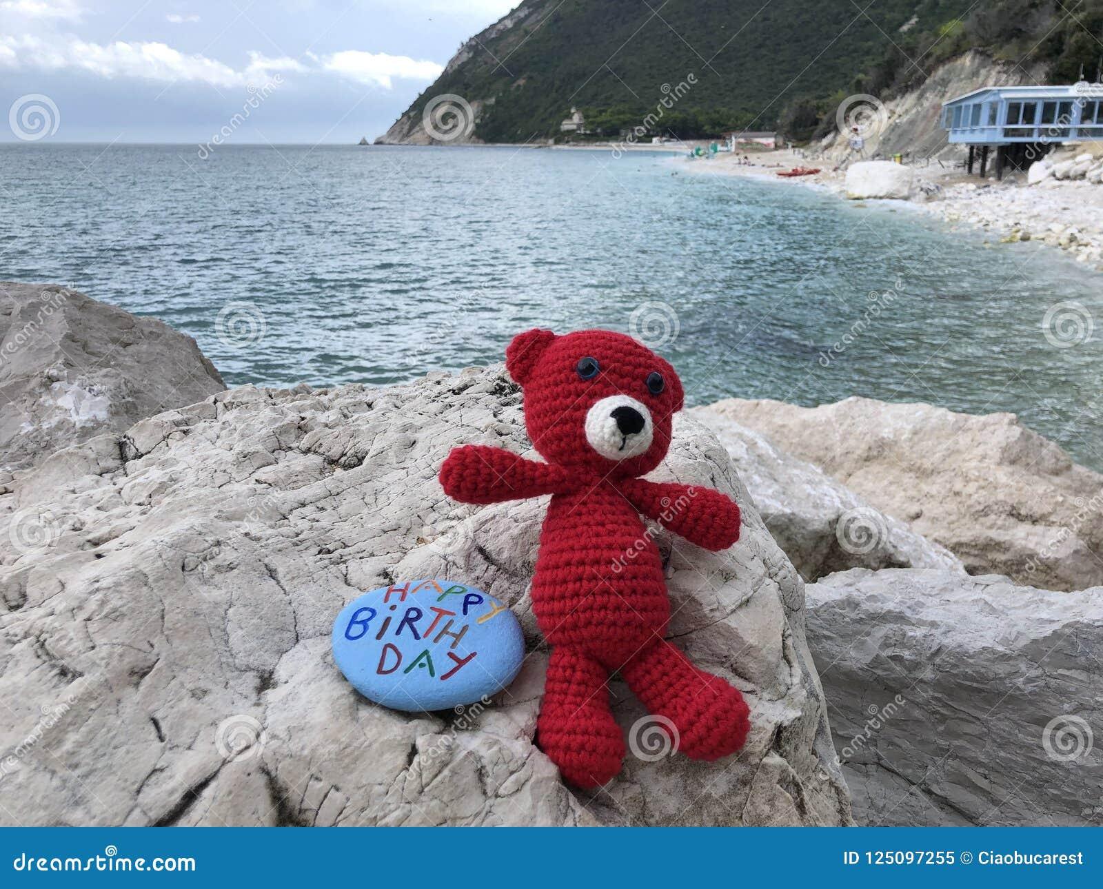 El mensaje del feliz cumpleaños en una piedra con una lana roja lleva