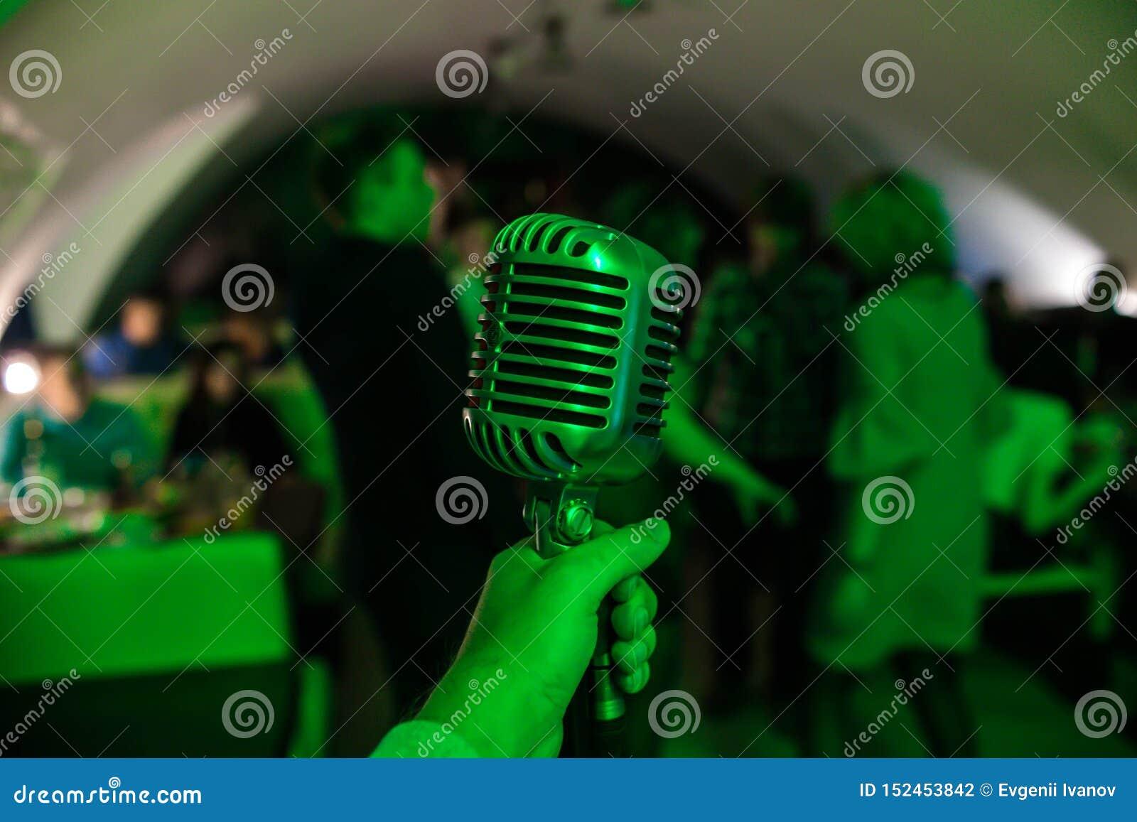 El micrófono está en etapa en un club nocturno El cantante se sostiene y canta en el micrófono Luz brillante del brillo del club