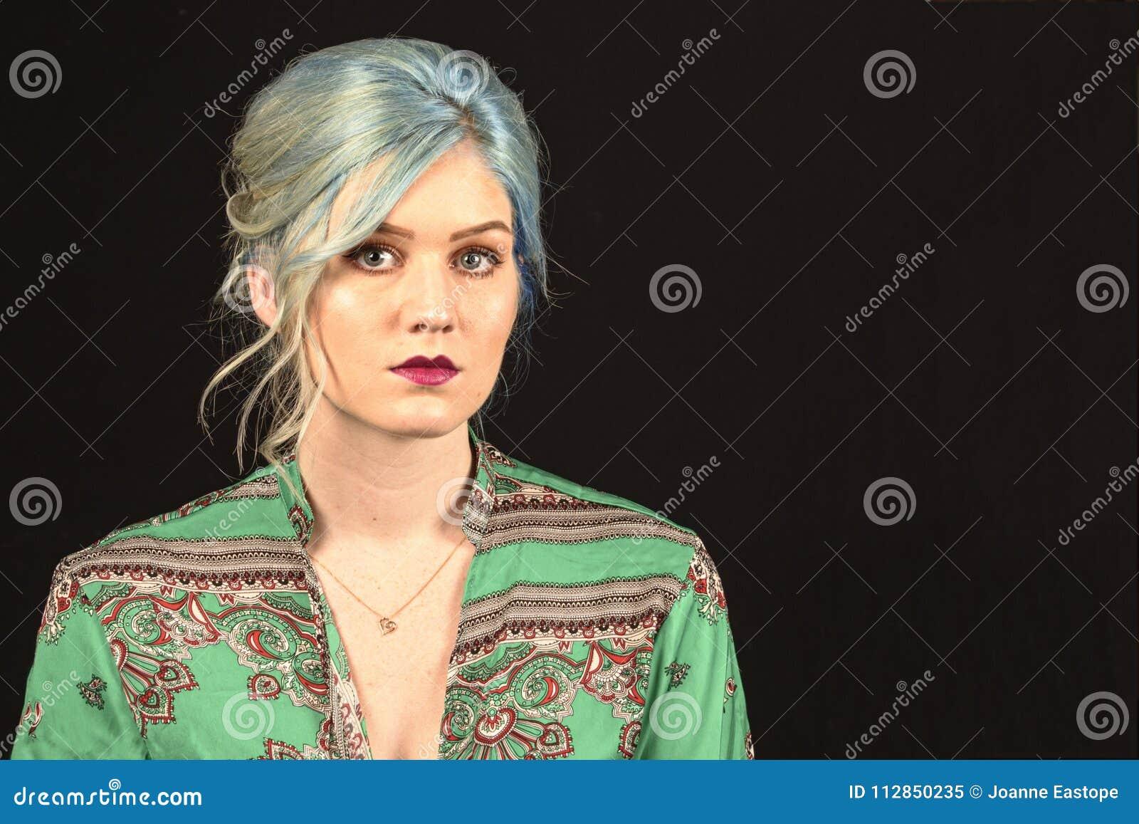 El modelo femenino caucásico, edad 22, azul teñió el pelo, la camisa roja de los labios, verde y roja Aislado en fondo negro Tors