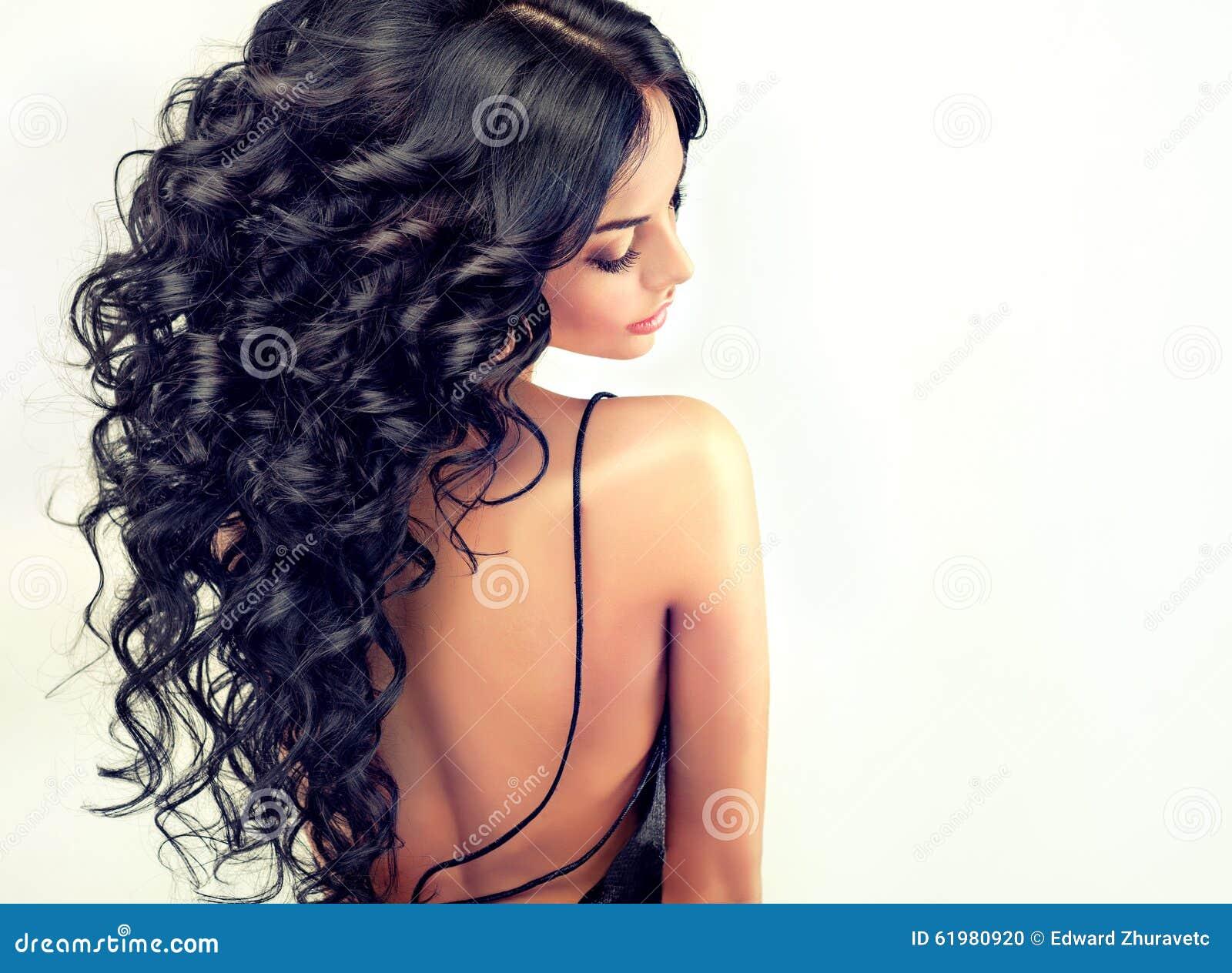El modelo hermoso de la muchacha del retrato con negro largo encrespó el pelo