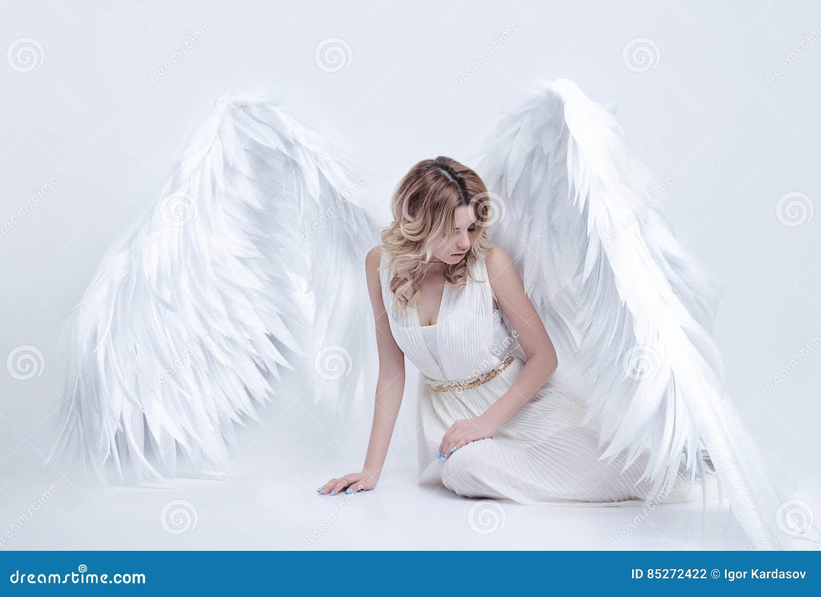 El modelo joven hermoso con ángel grande se va volando sentarse en el estudio