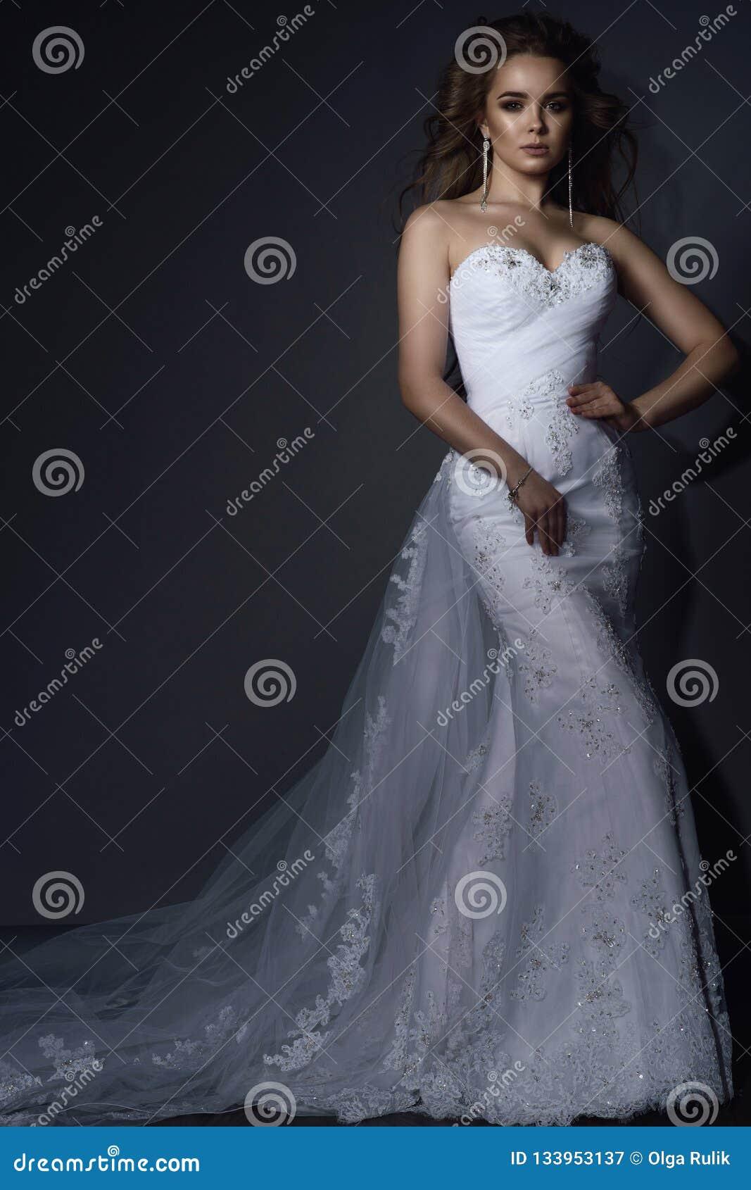El modelo joven hermoso con perfecto compone y pelo que sopla que lleva el vestido de boda blanco del cordón de la sirena lujosa