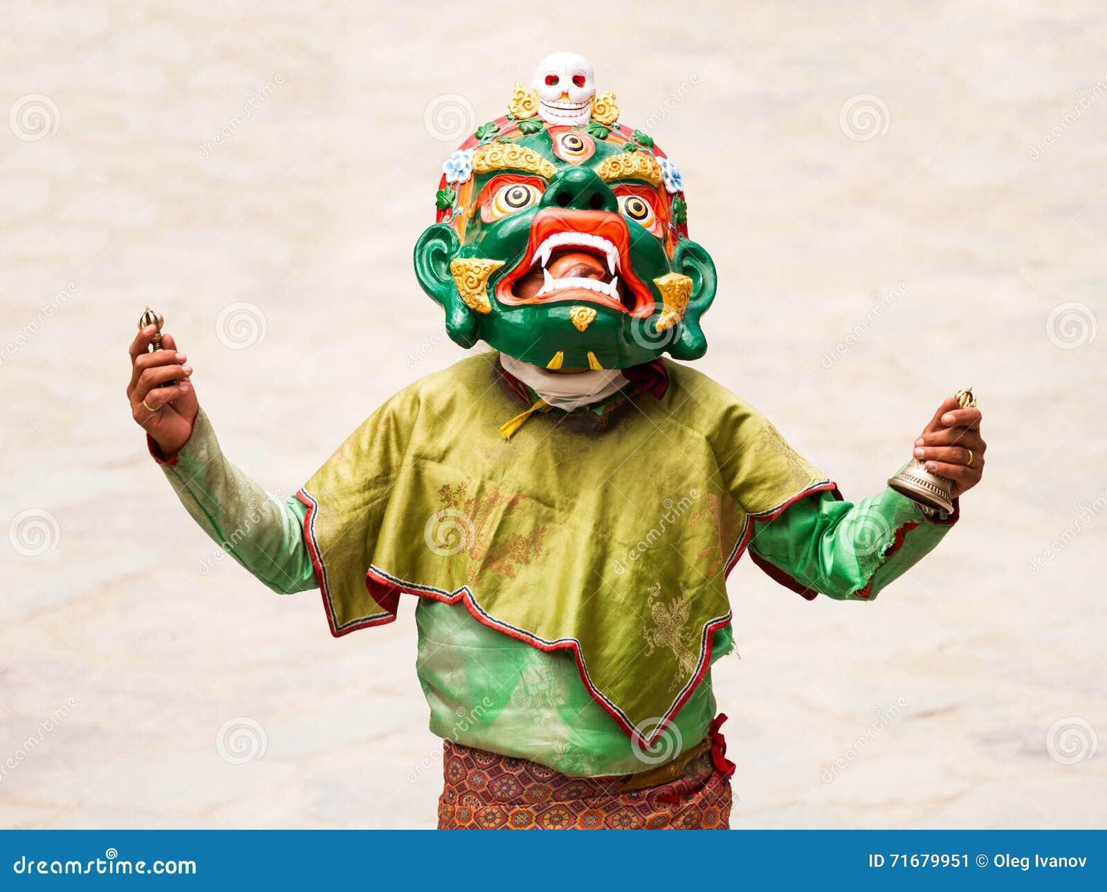 El monje no identificado con la campana y el vajra rituales realiza una danza enmascarada y vestida religiosa del misterio del bu