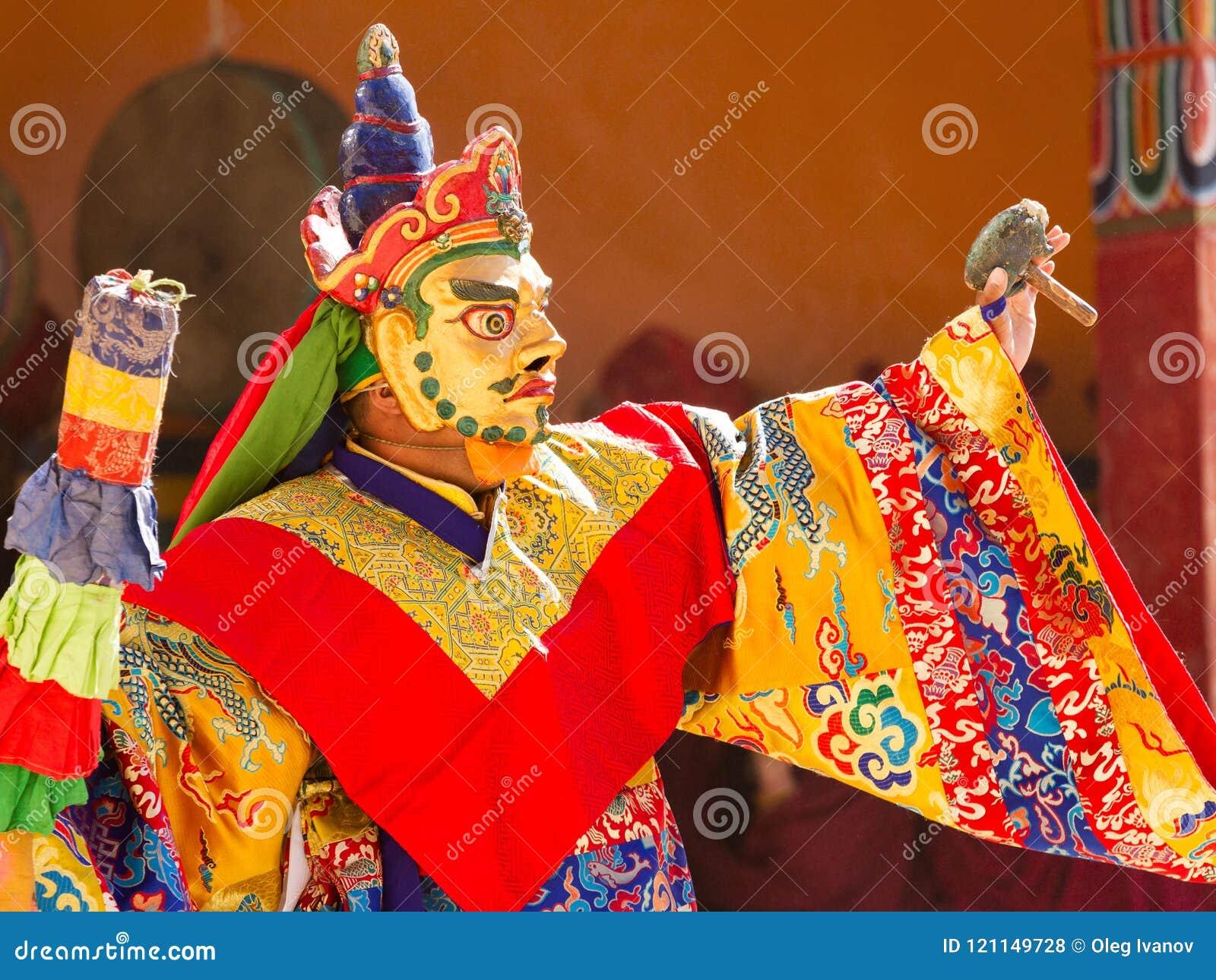 El monje realiza una danza sagrada enmascarada y vestida del tibetano Budd