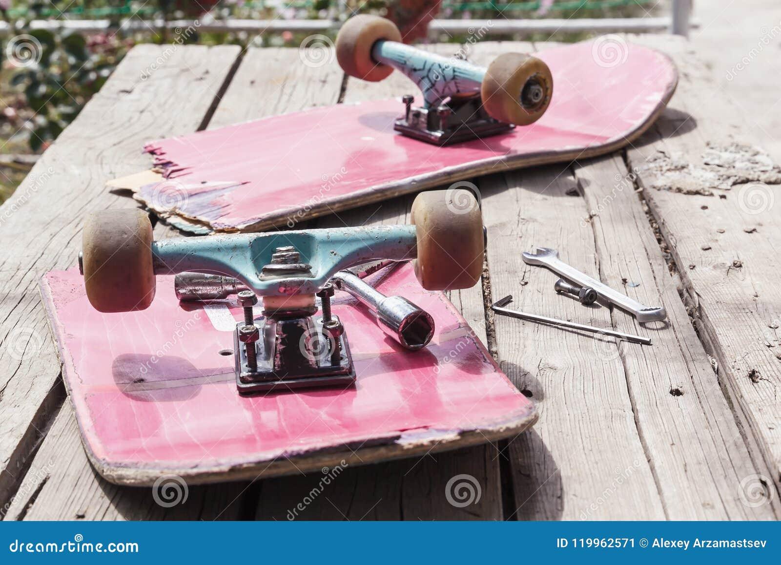 El monopatín roto viejo miente con una llave inglesa en una tabla de madera en el aire abierto