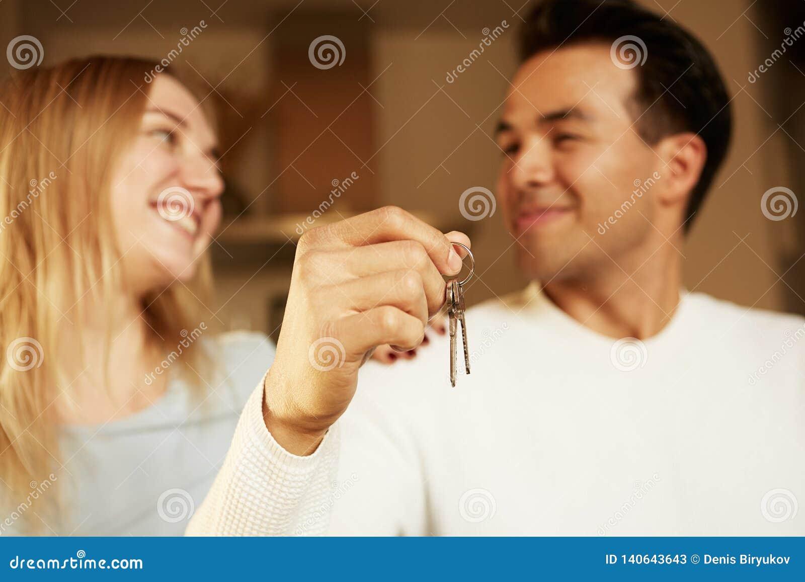 El mostrar joven sonriente feliz de los pares llaves de su nueva casa