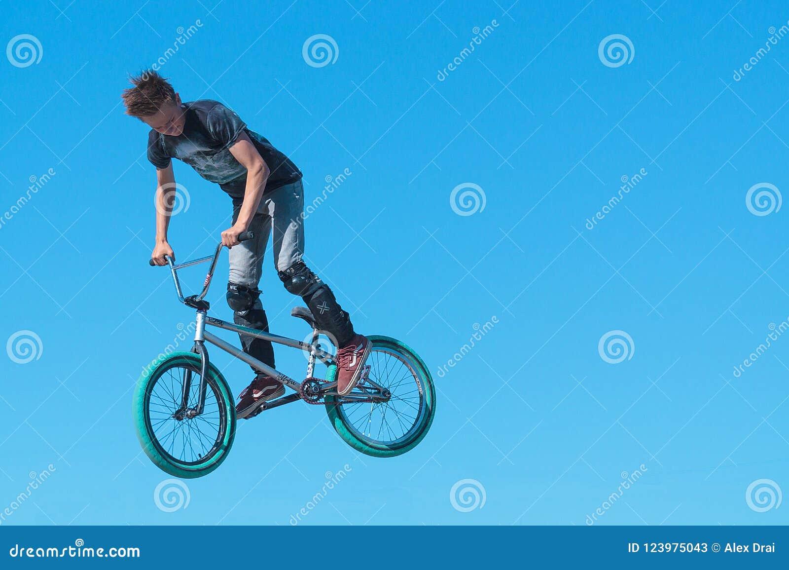 El motorista joven de BMX con la pierna protege en BMX que hace truco del aire