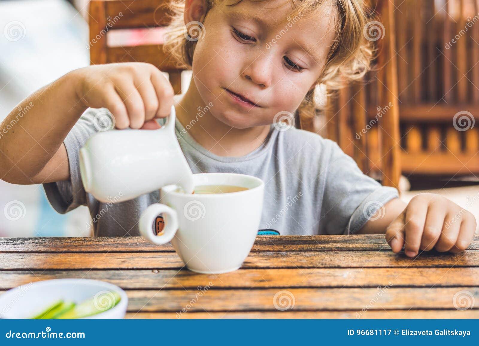 El muchacho agradable feliz vierte la miel en el té en jardín del verde del verano