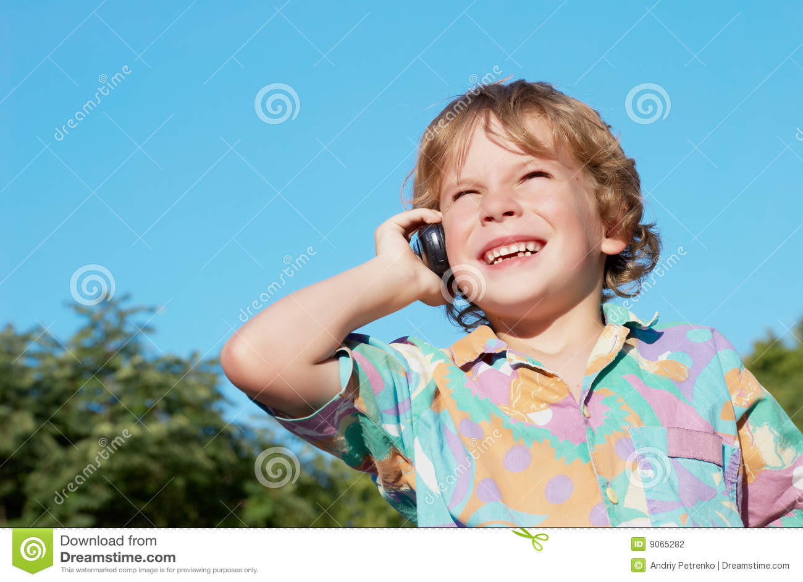 El muchacho alegre con un teléfono móvil