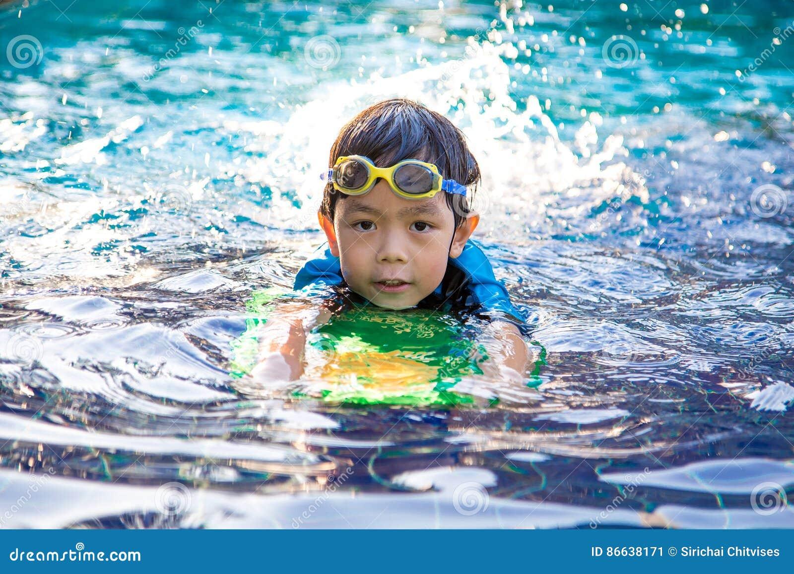 El muchacho aprende nadar en la piscina