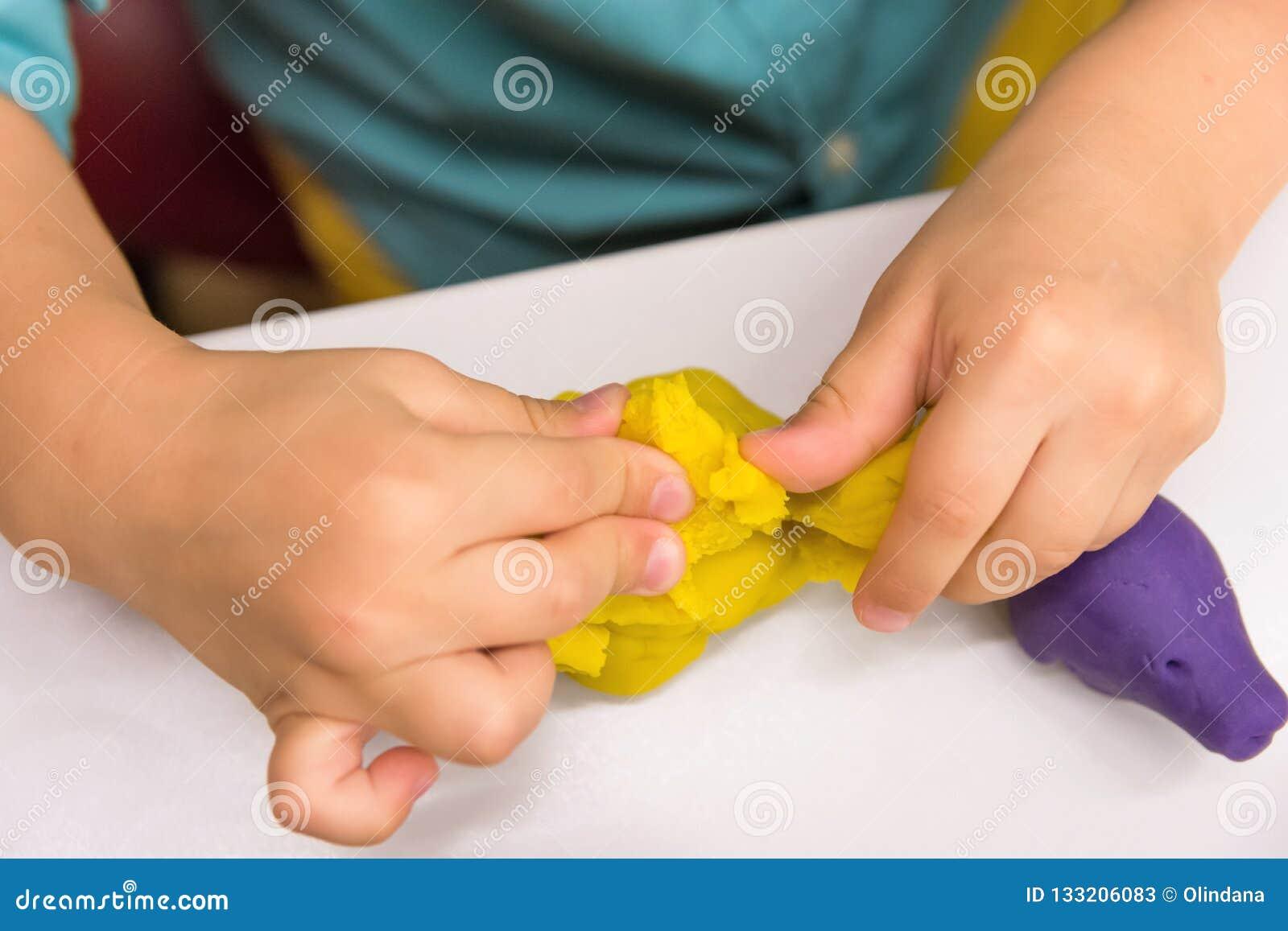 El muchacho caucásico año cuatro hace con las figuras animales de las manos de modelar la arcilla amarilla en el tablero de la me