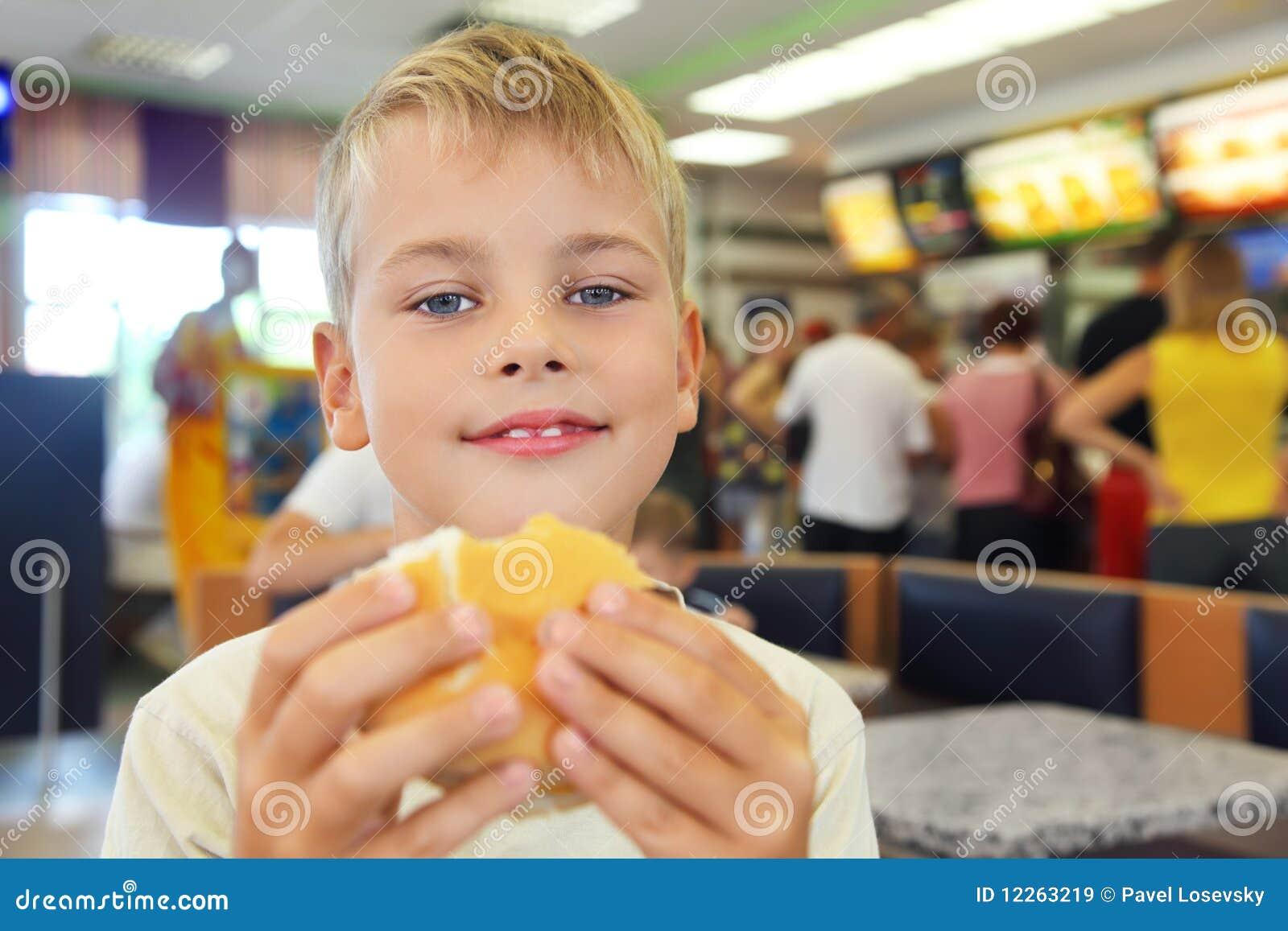 El muchacho come la hamburguesa