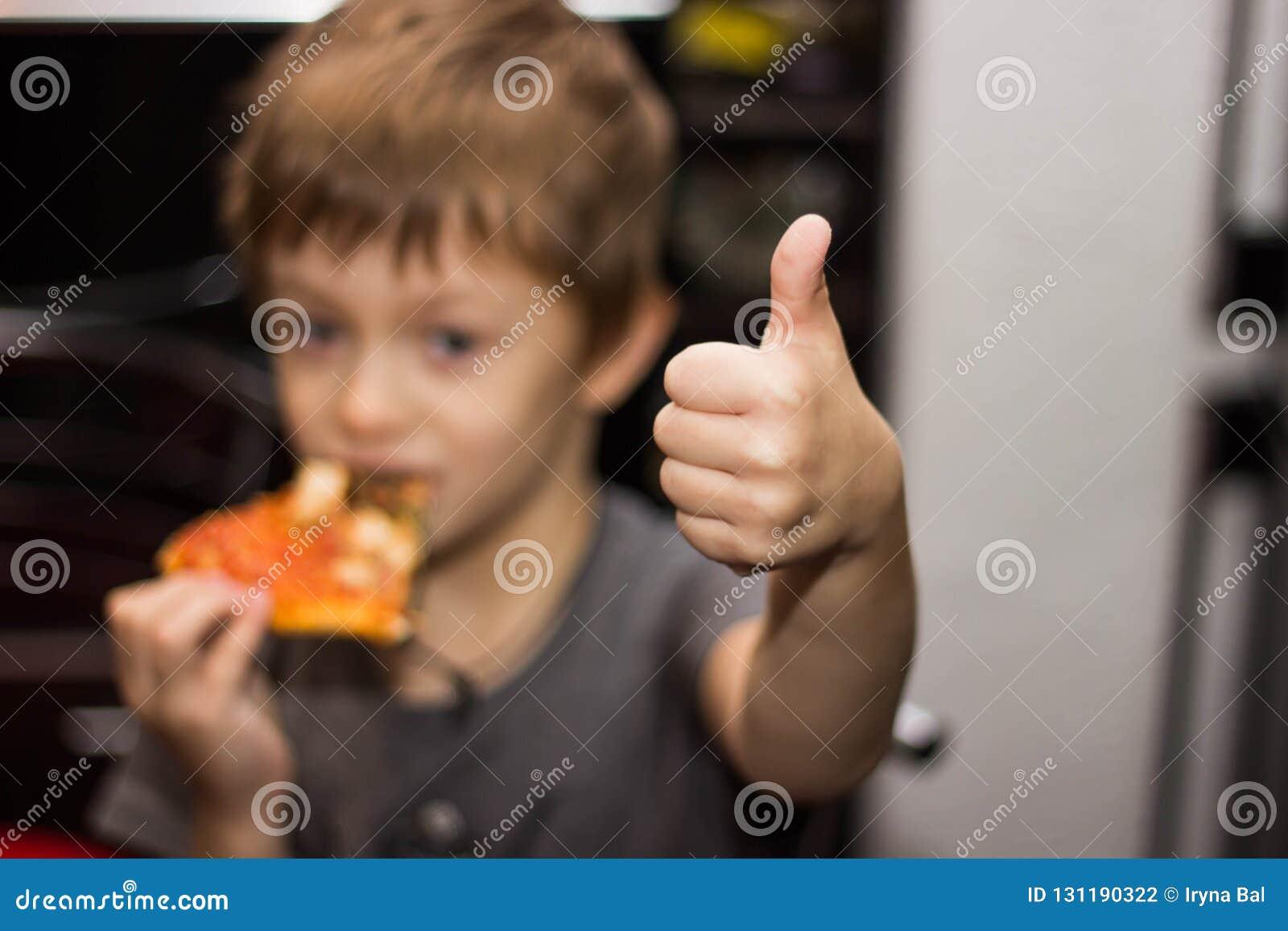 El muchacho come una pizza muy sabrosa con gran placer