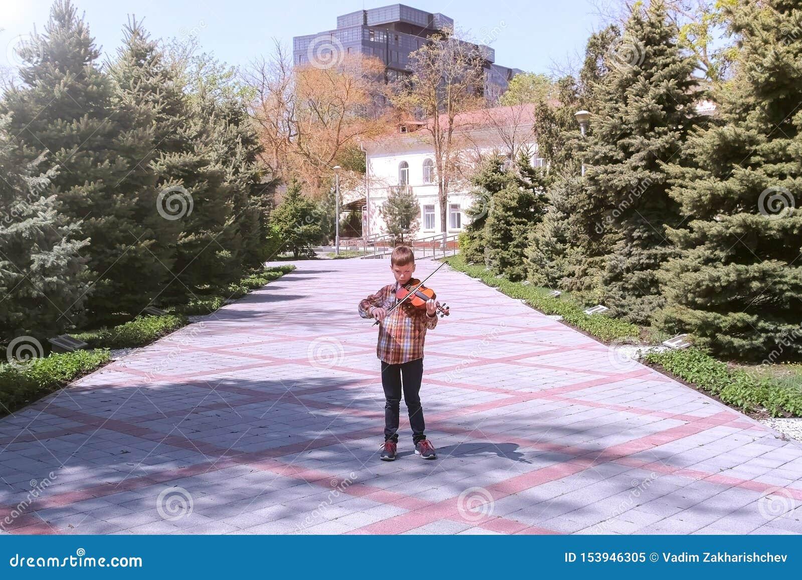 El muchacho del niño está jugando la situación del violín en el callejón en la calle en la ciudad