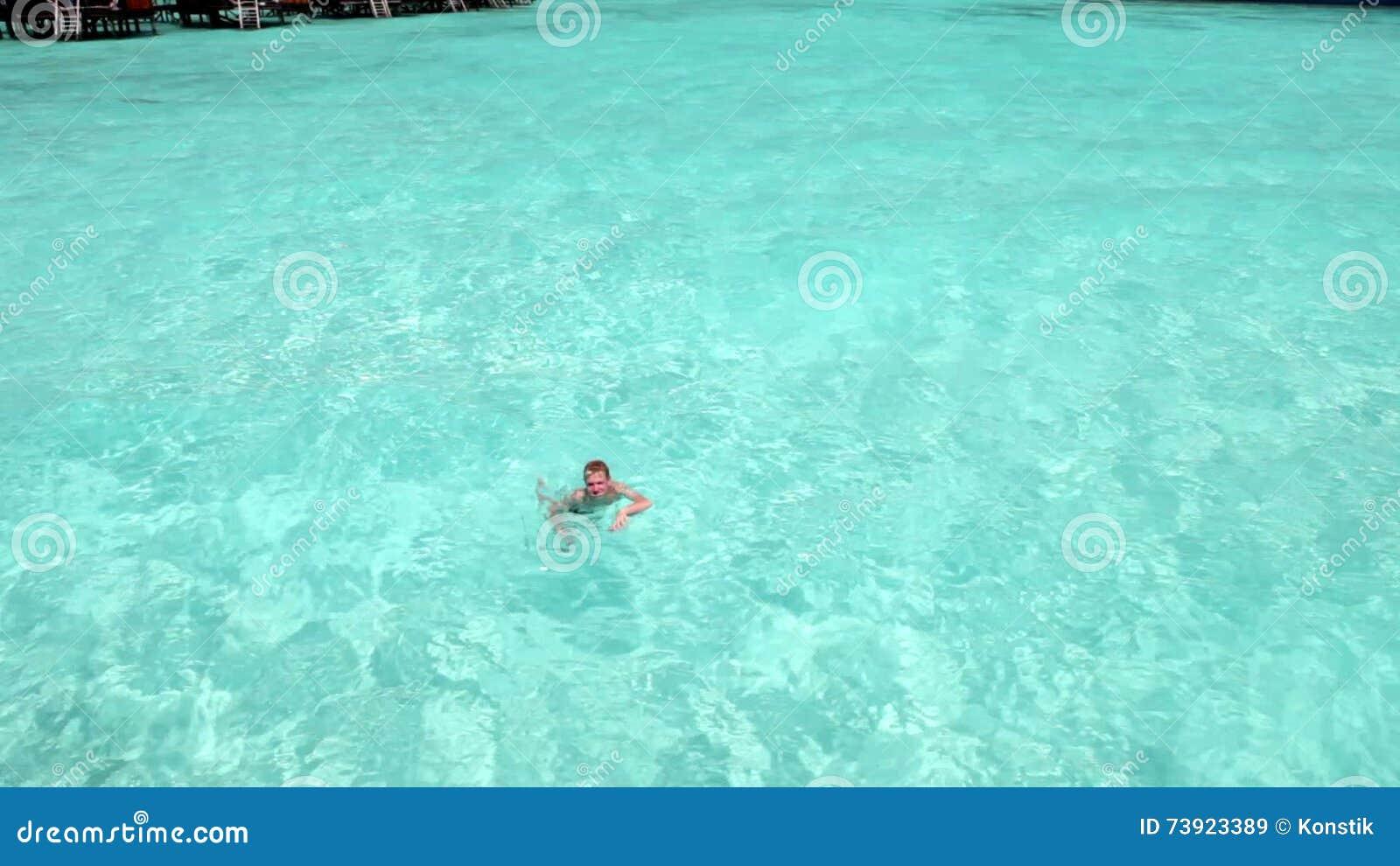 El Muchacho, El Adolescente, Nadando En El Agua Transparente