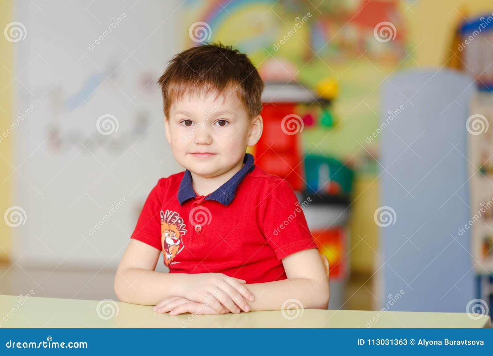 El muchacho en una camiseta roja se sienta en un escritorio en una guardería