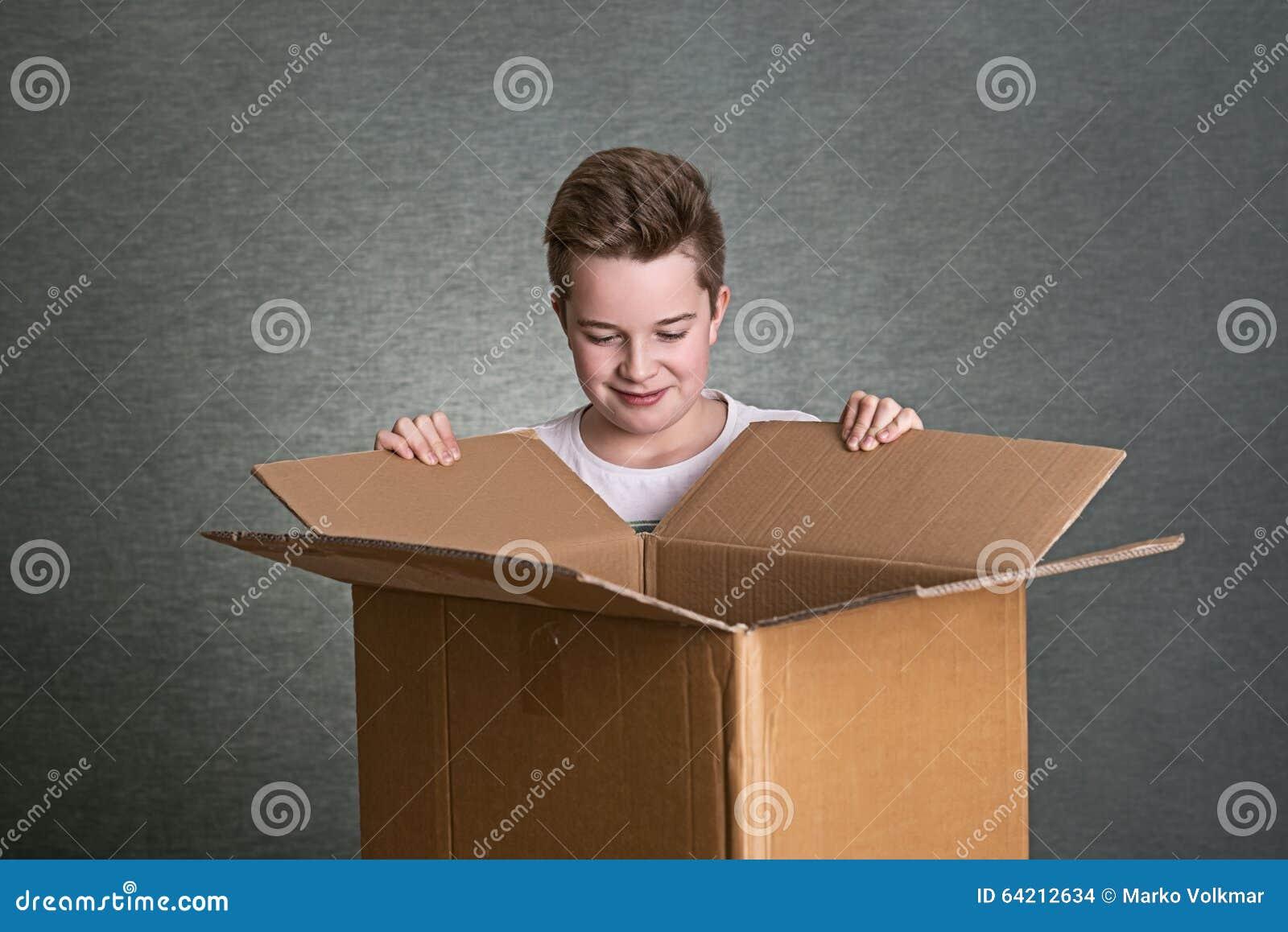 El muchacho está mirando en una caja de cartón
