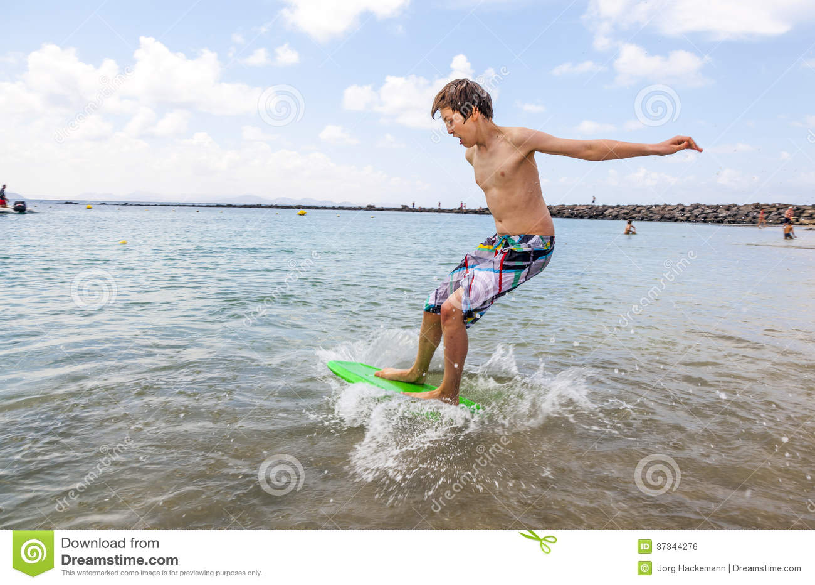 El muchacho feliz goza el practicar surf en las ondas