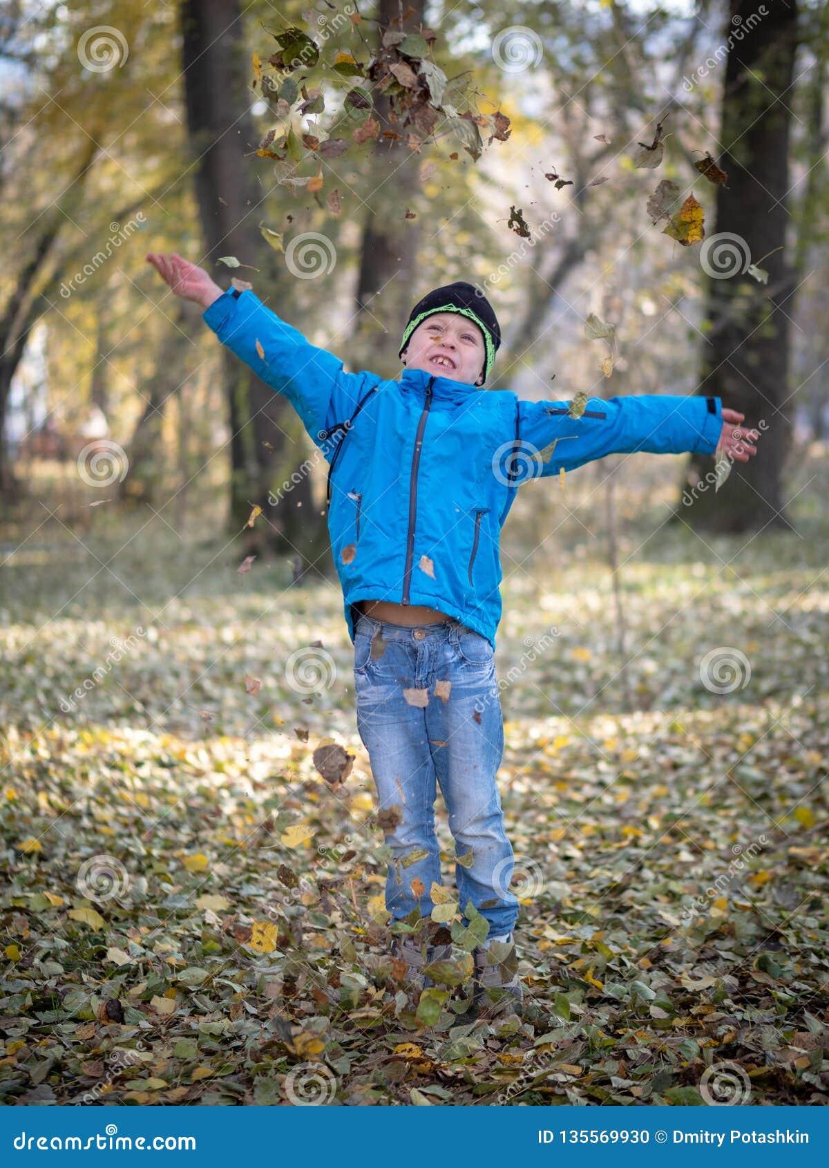 El muchacho feliz lanza las hojas en parque del otoño