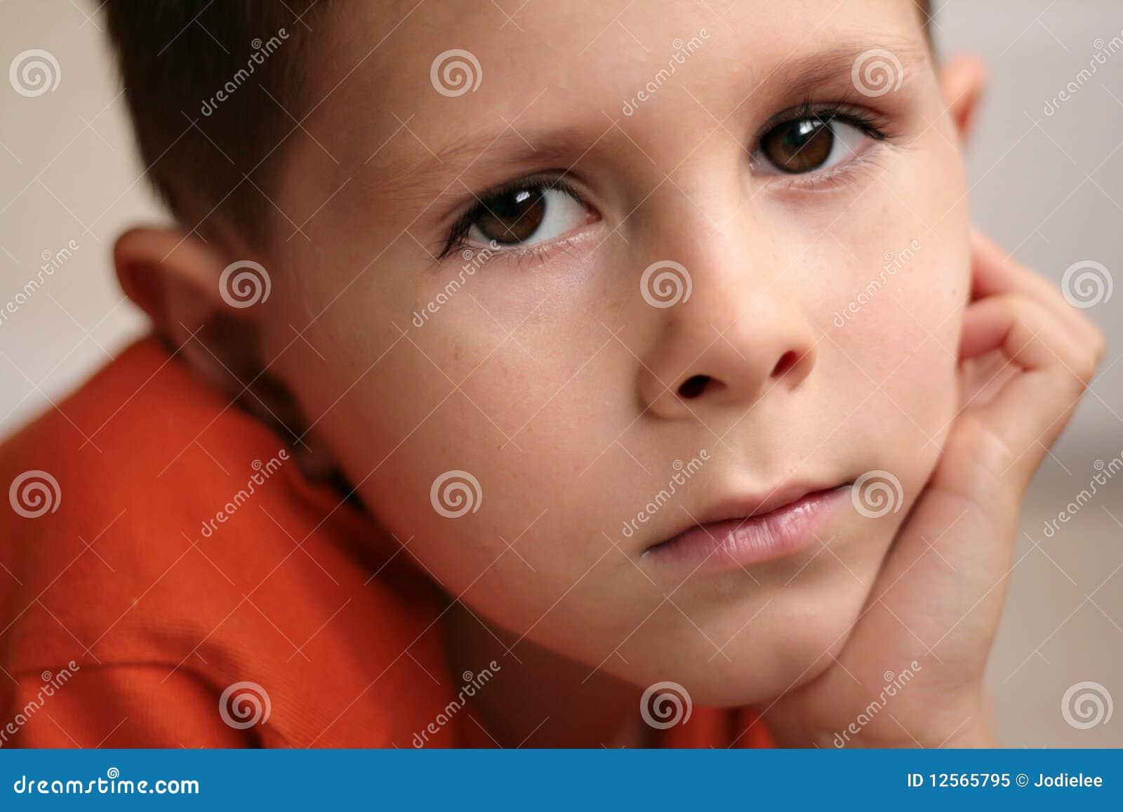 El muchacho joven relajó la sonrisa con las manos en la barbilla