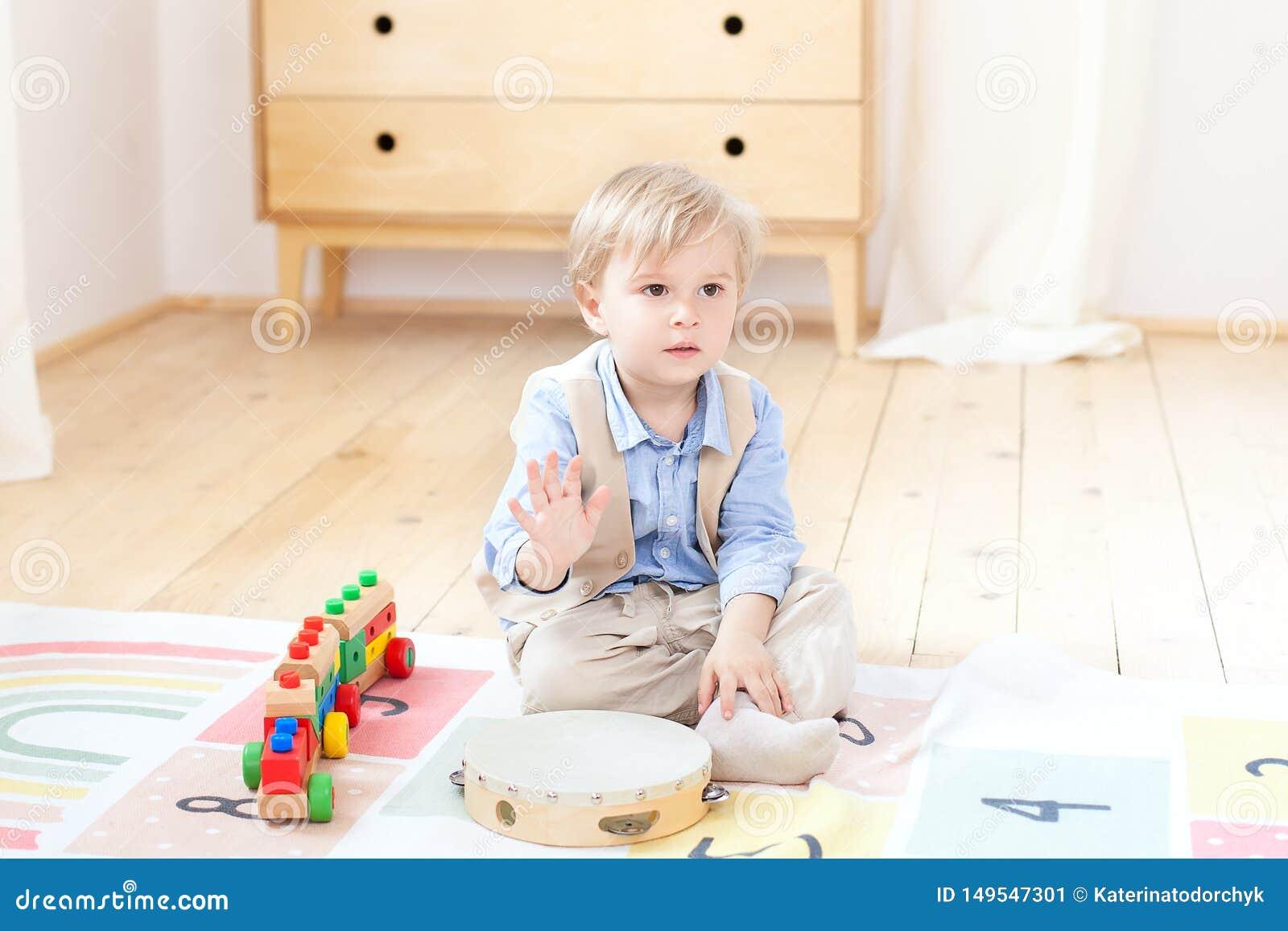 El muchacho juega con un tambor de madera musical y un tren Juguetes de madera educativos para el niño Retrato de un muchacho que