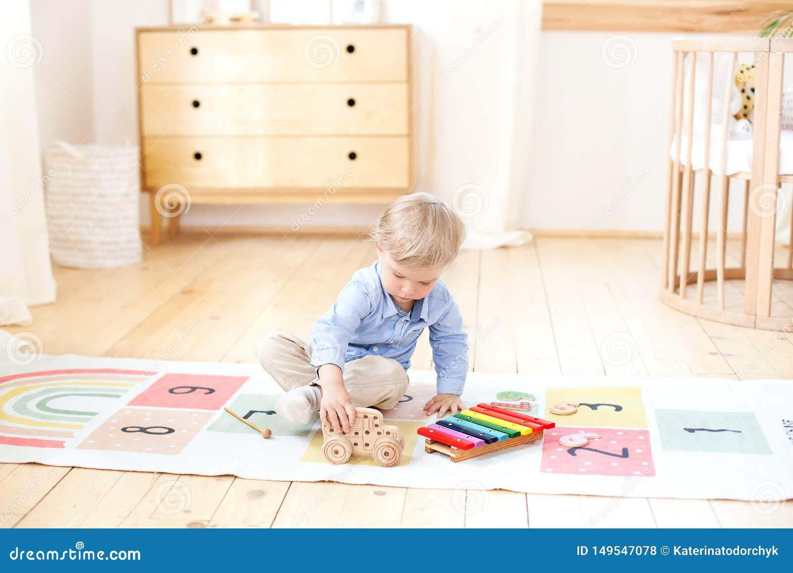 El muchacho juega con una máquina de escribir de madera Juguetes de madera educativos para el niño Retrato de un muchacho que se