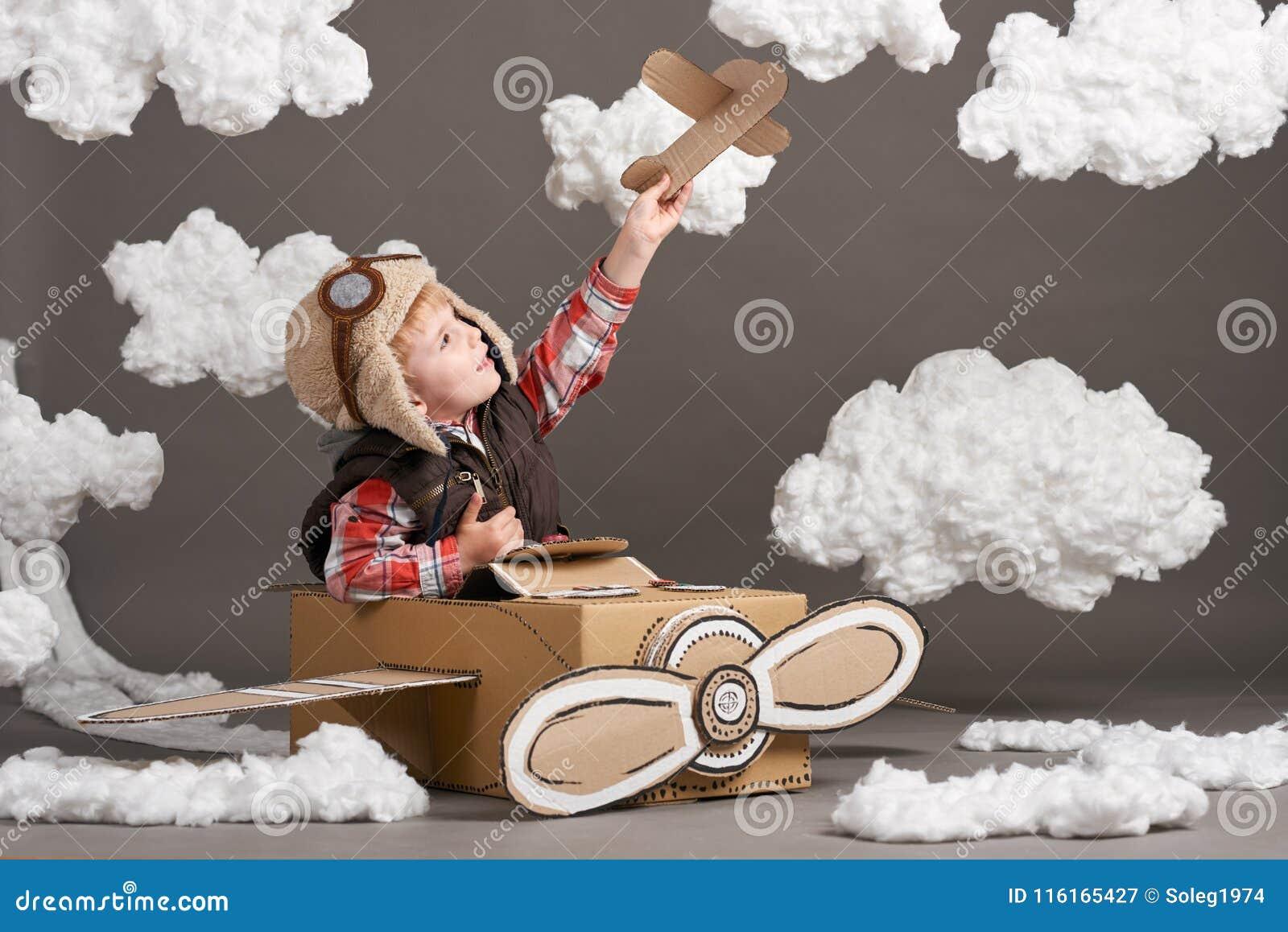El muchacho juega en un aeroplano hecho de la caja de cartón y de sueños de hacer piloto, nubes de la algodón en un fondo gris