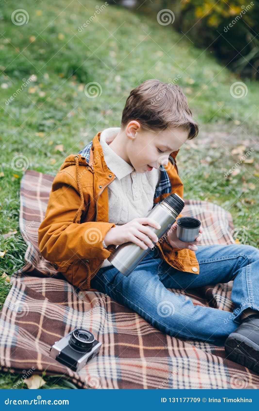 El muchacho lindo camina y presenta en un parque colorido del otoño