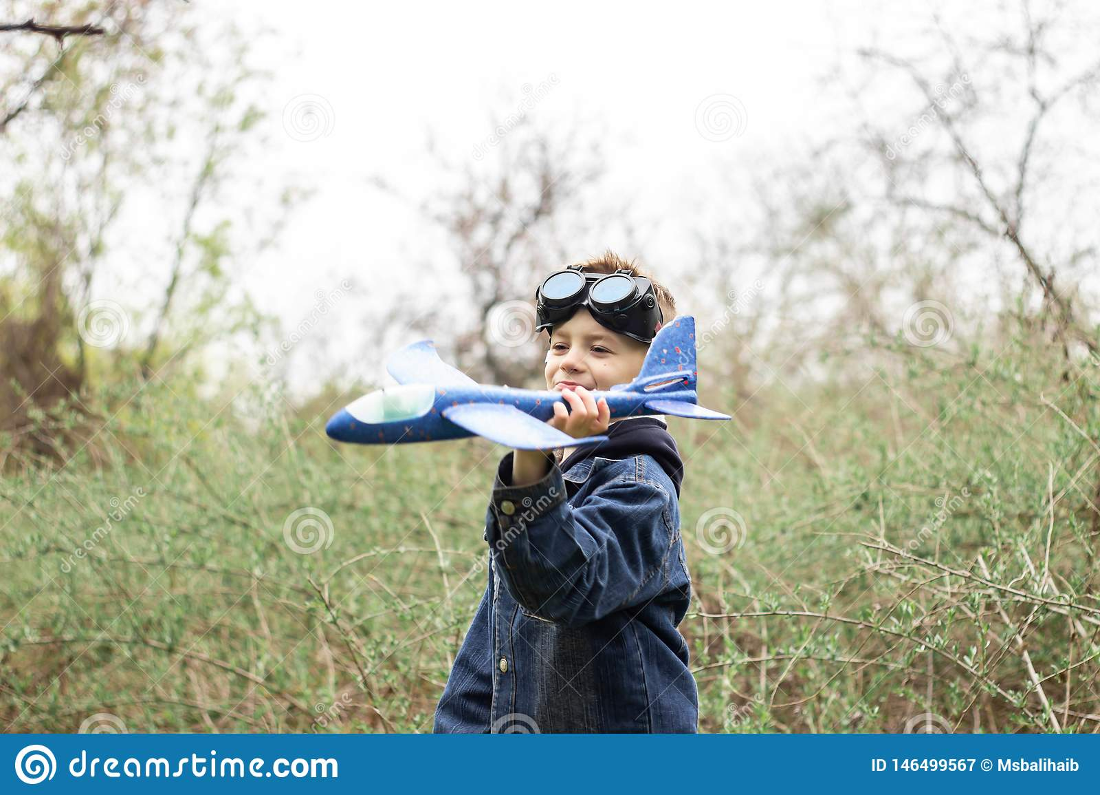 El muchacho pone en marcha un avi?n azul en el cielo en un bosque denso