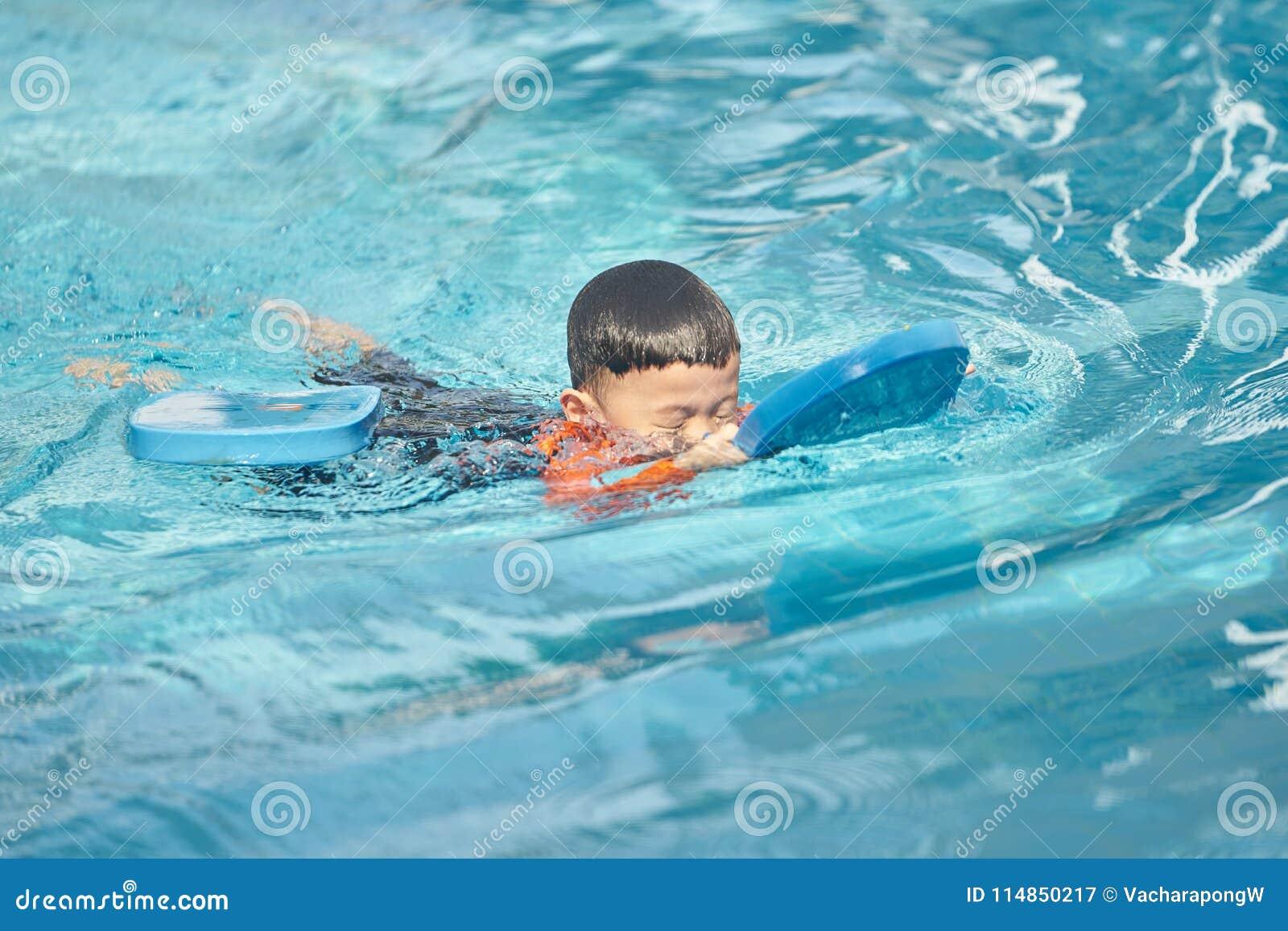 El muchacho practica el nadar con el flotador del cojín de goma espuma en agua