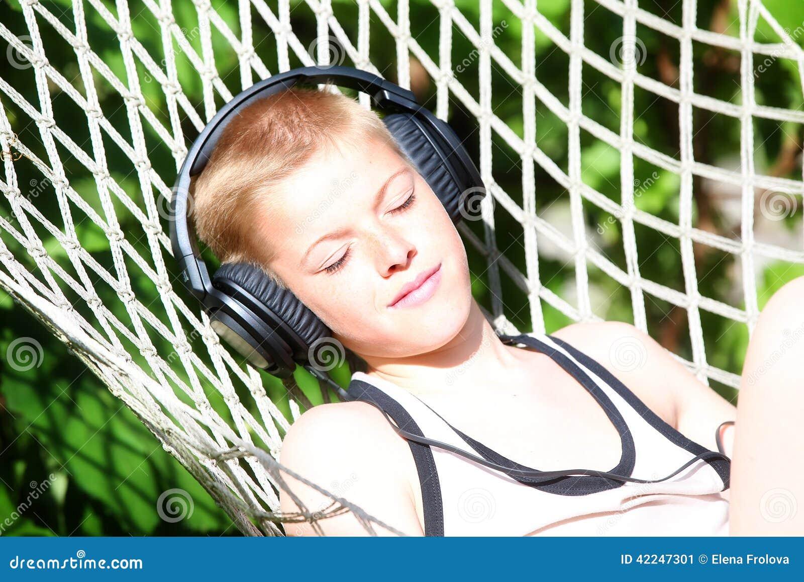 El muchacho que miente en una hamaca y escucha la música en los auriculares Verano