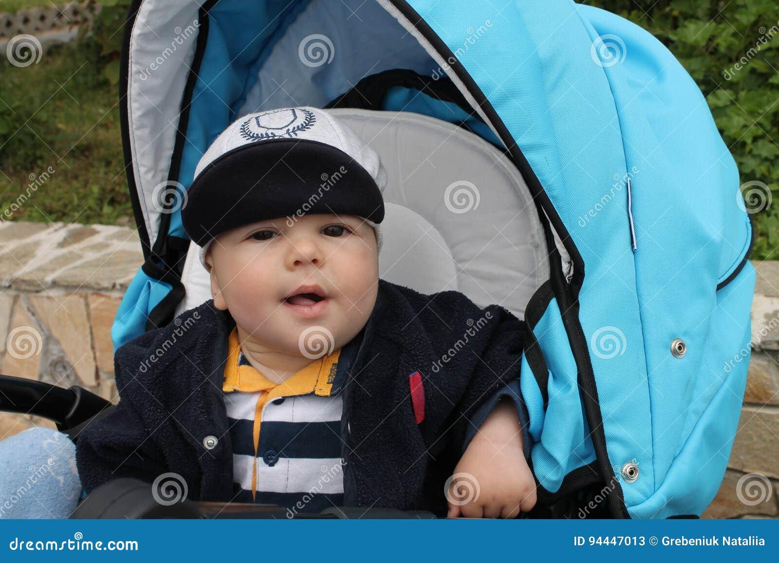 El muchacho relajado en el stoller azul