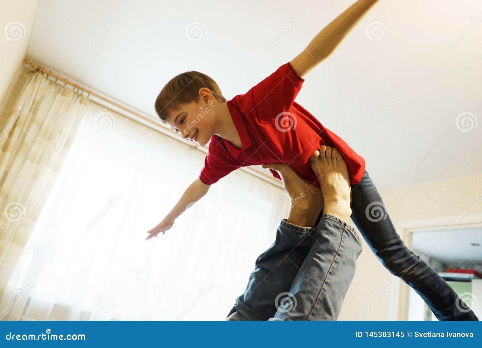 El muchacho representa un avi?n con los brazos extendidos, apoyado en las piernas de su padre