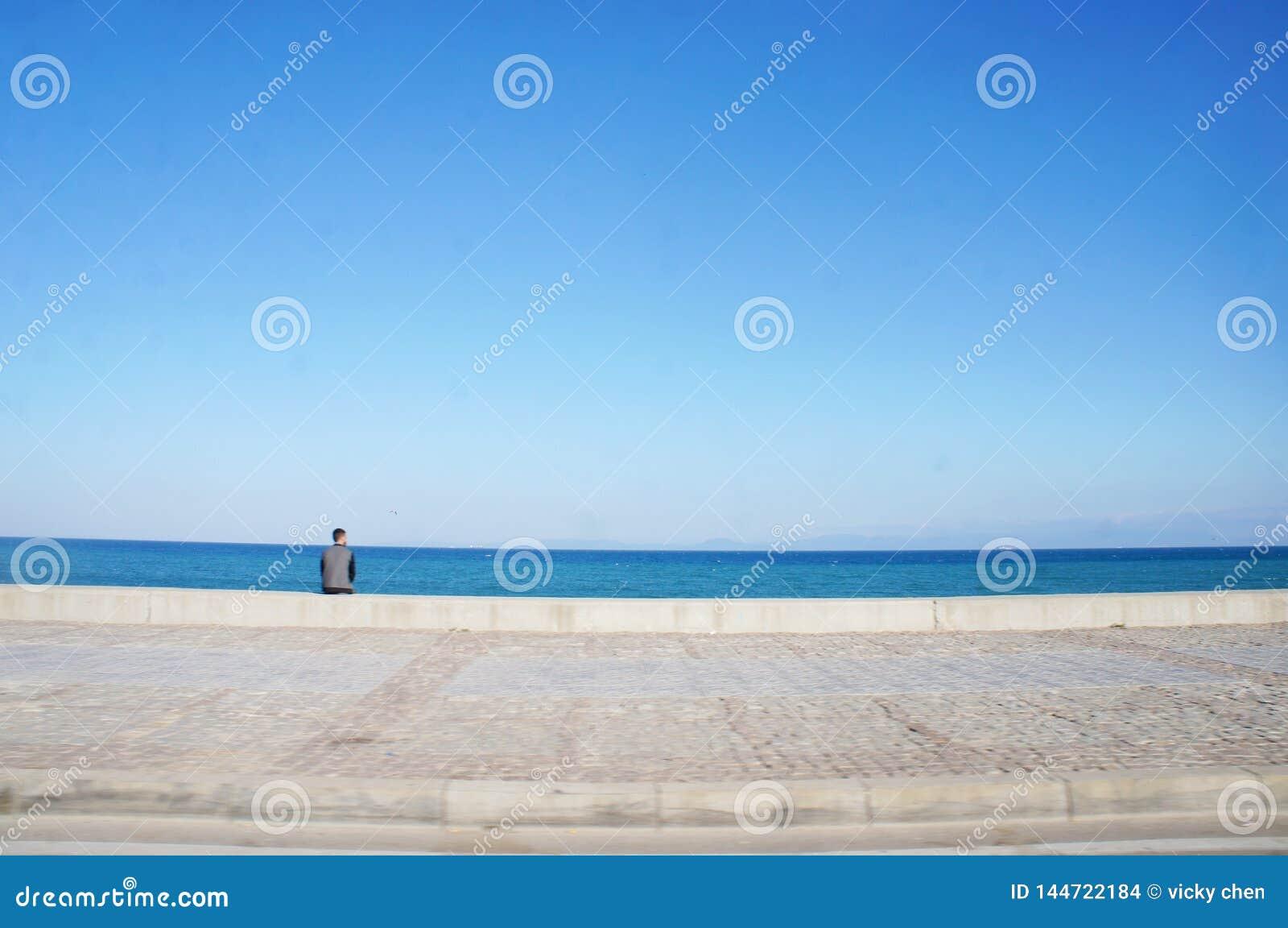 El muchacho se sentó al lado de la playa en Tánger