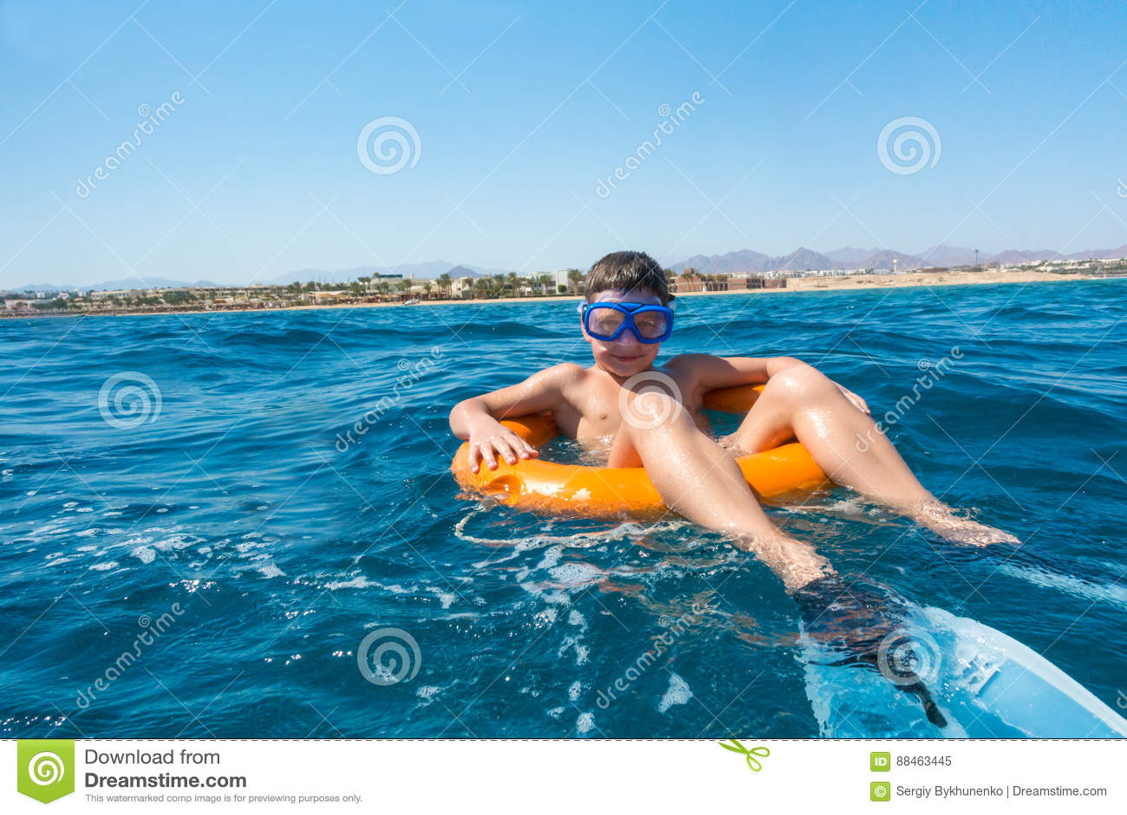 El muchacho sonriente aprende nadar en salvavidas en el mar