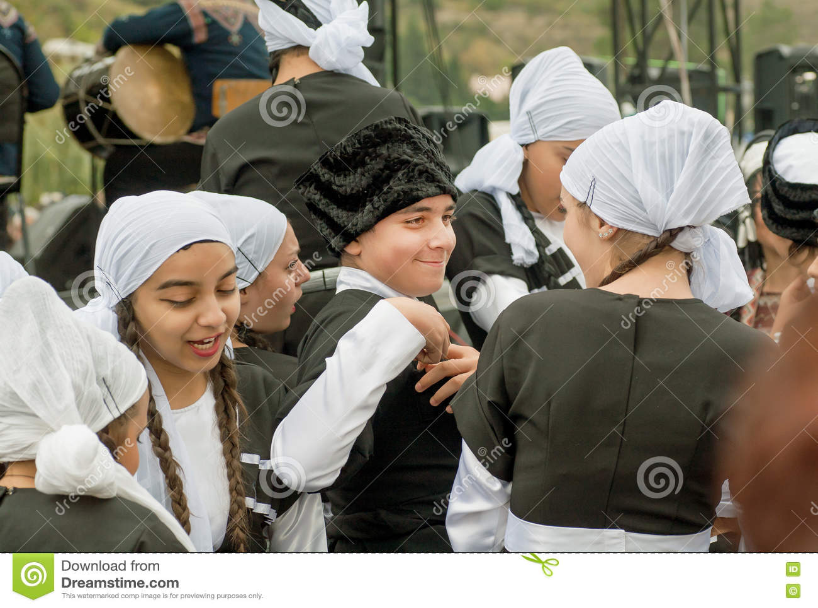 El muchacho y las muchachas lindas en los trajes georgianos tradicionales que van a la celebración van de fiesta