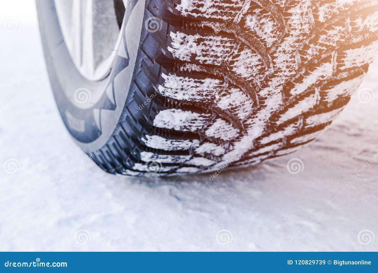 El neumático de coche en el cierre de la nieve para arriba Pistas del coche en la nieve Rastros del coche en la nieve Neumáticos