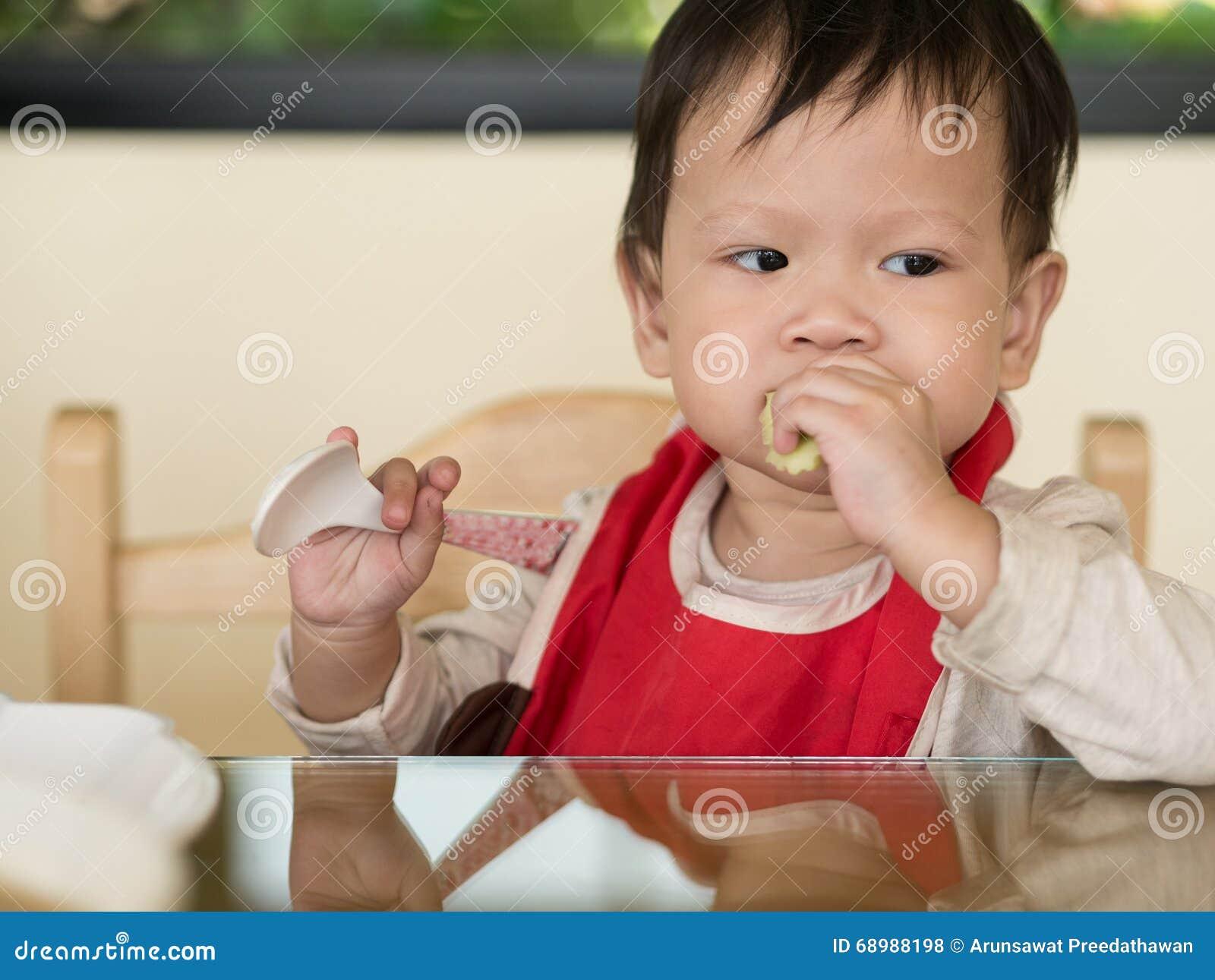 El niño asiático aprende comer la comida mismo