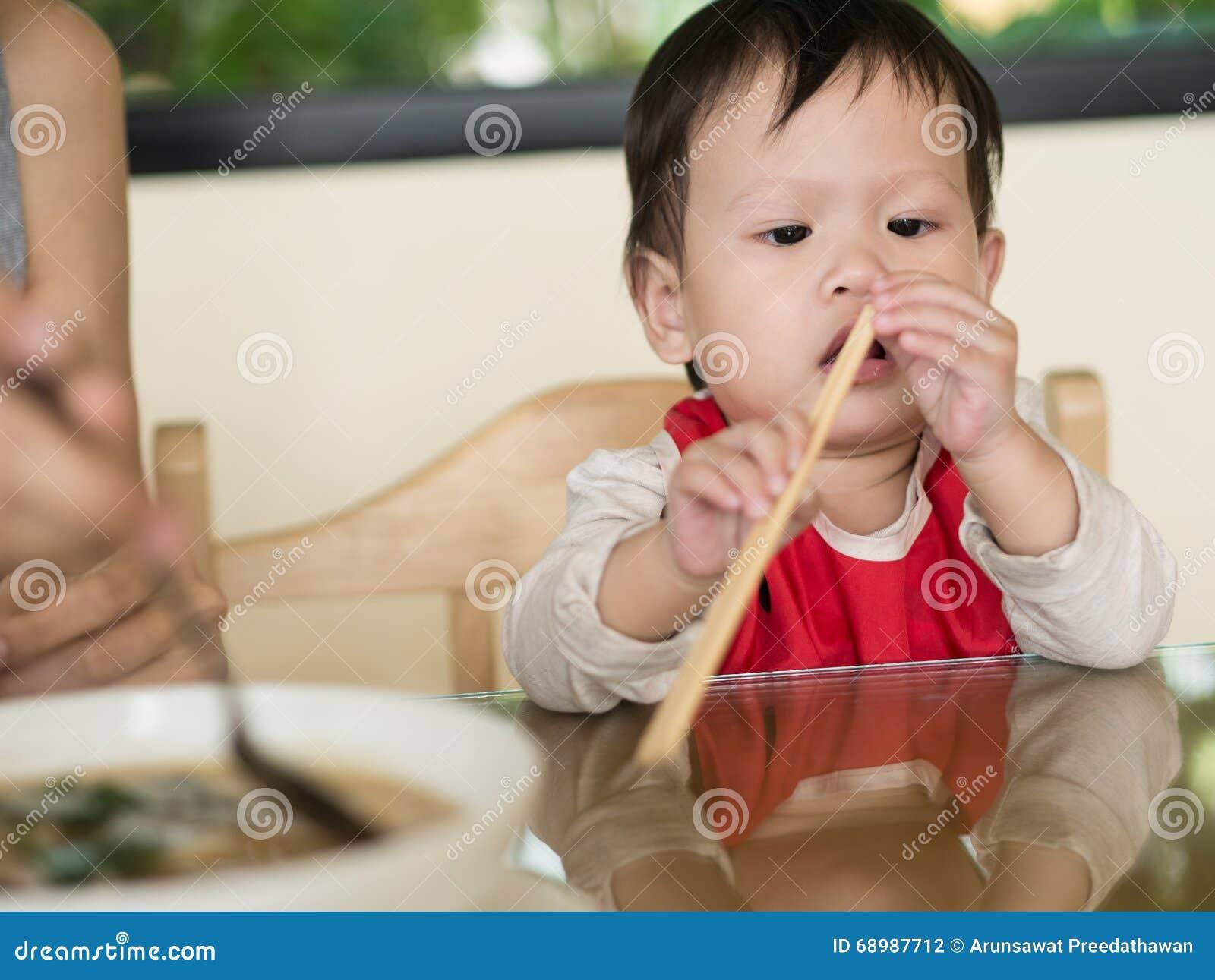 El niño asiático aprende comer la comida mismo que sostiene los palillos