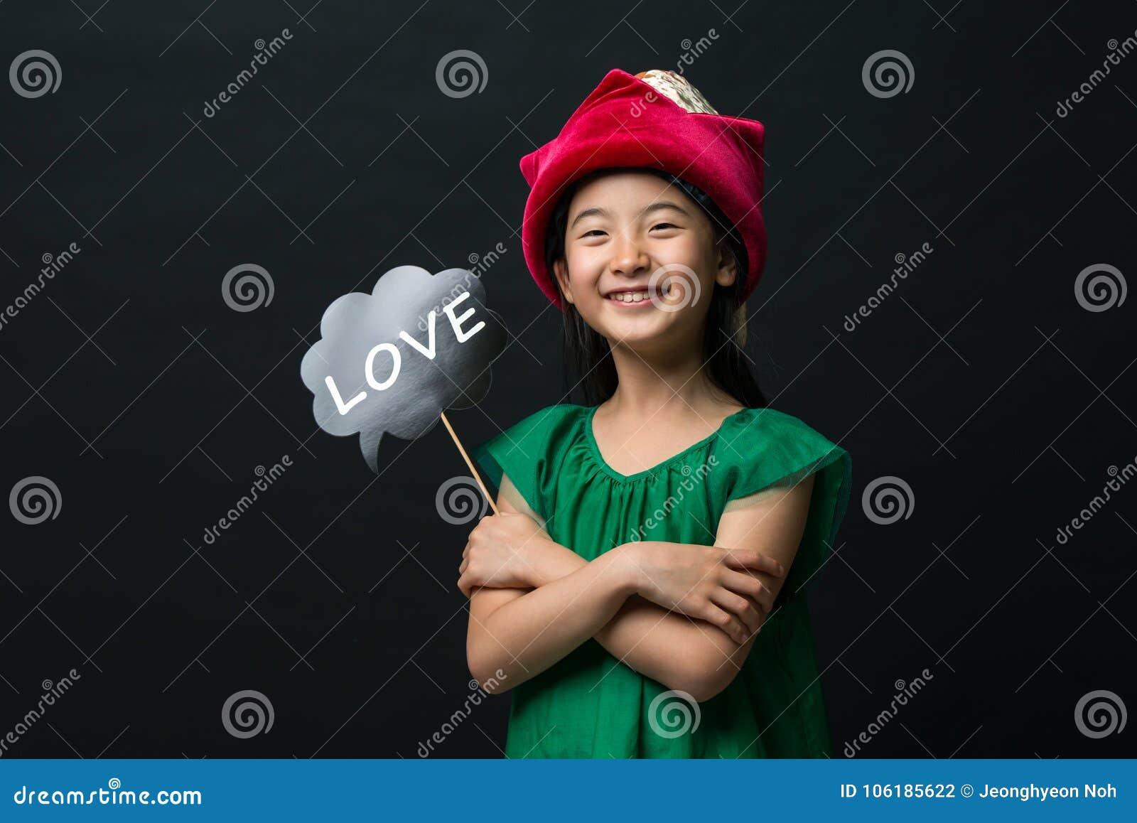 El niño asiático lindo de la muchacha se vistió en un vestido verde que sostenía un sombrero de la Navidad y un palillo del amor