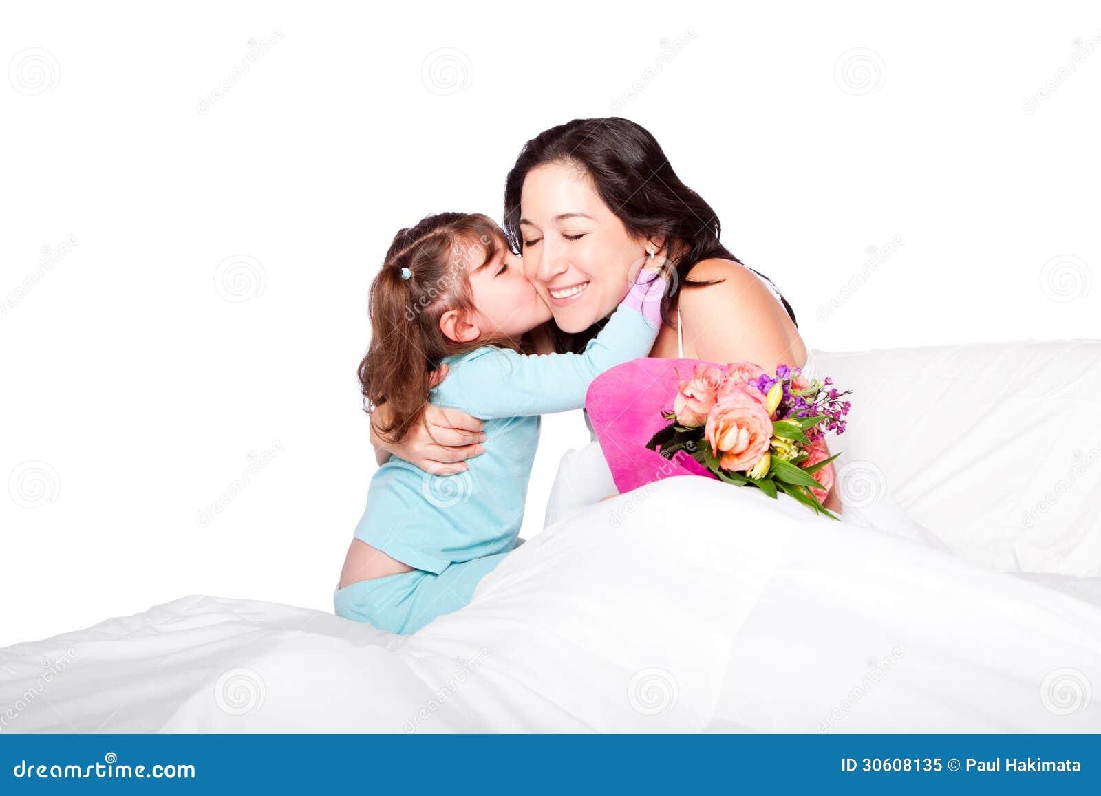 El niño da las flores y beso a la mamá en cama