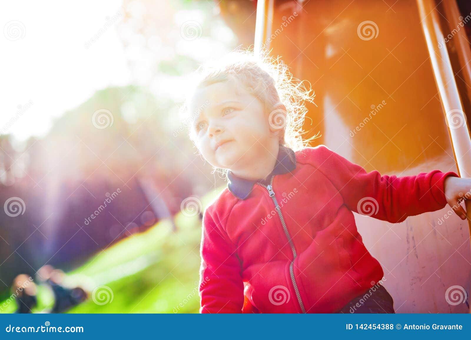 El niño de la muchacha juega en la diapositiva en el parque