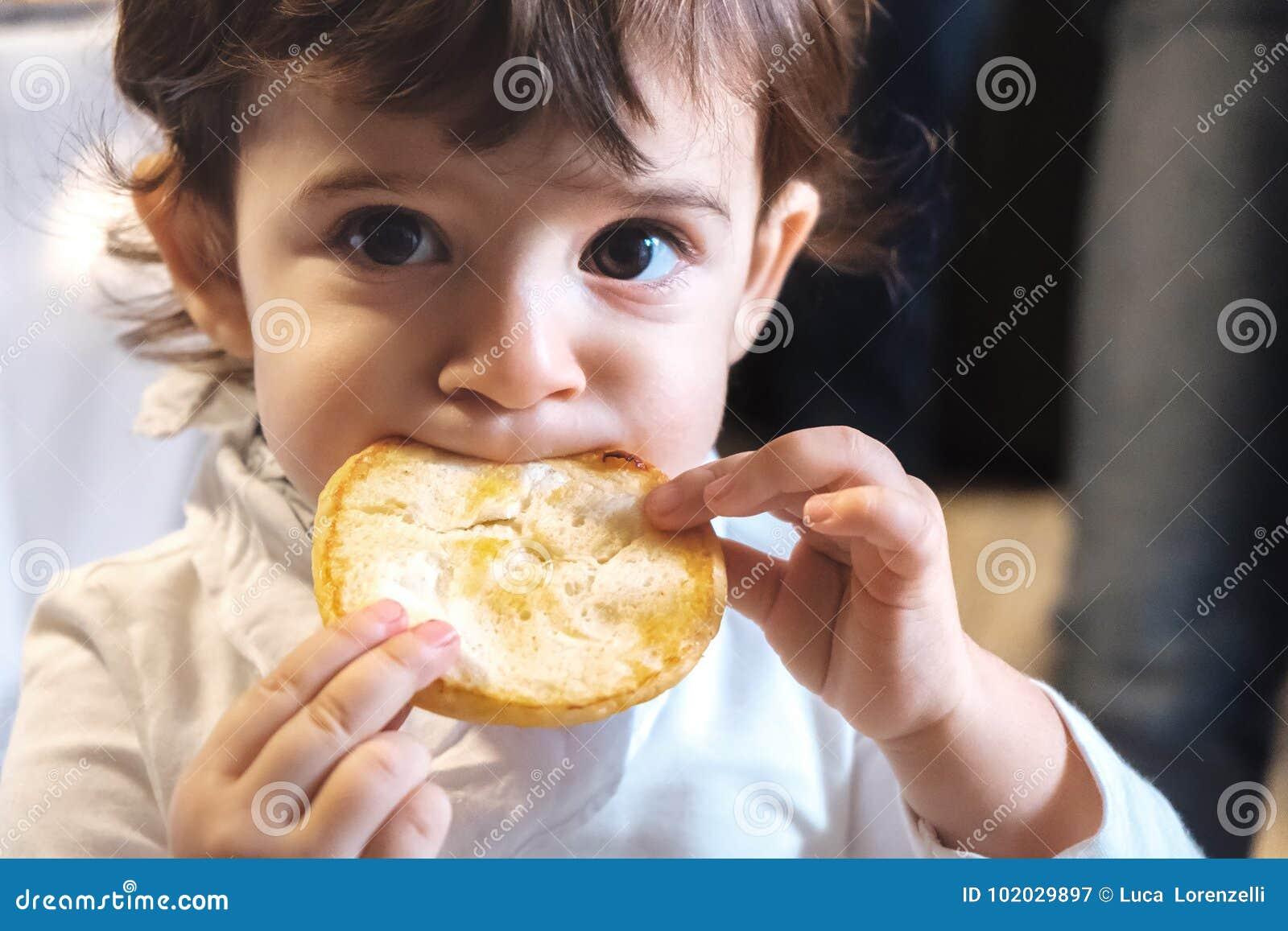El niño del bebé come la dieta malsana de la consumición de los carbohidratos de la cara del retrato recién nacido del primer par